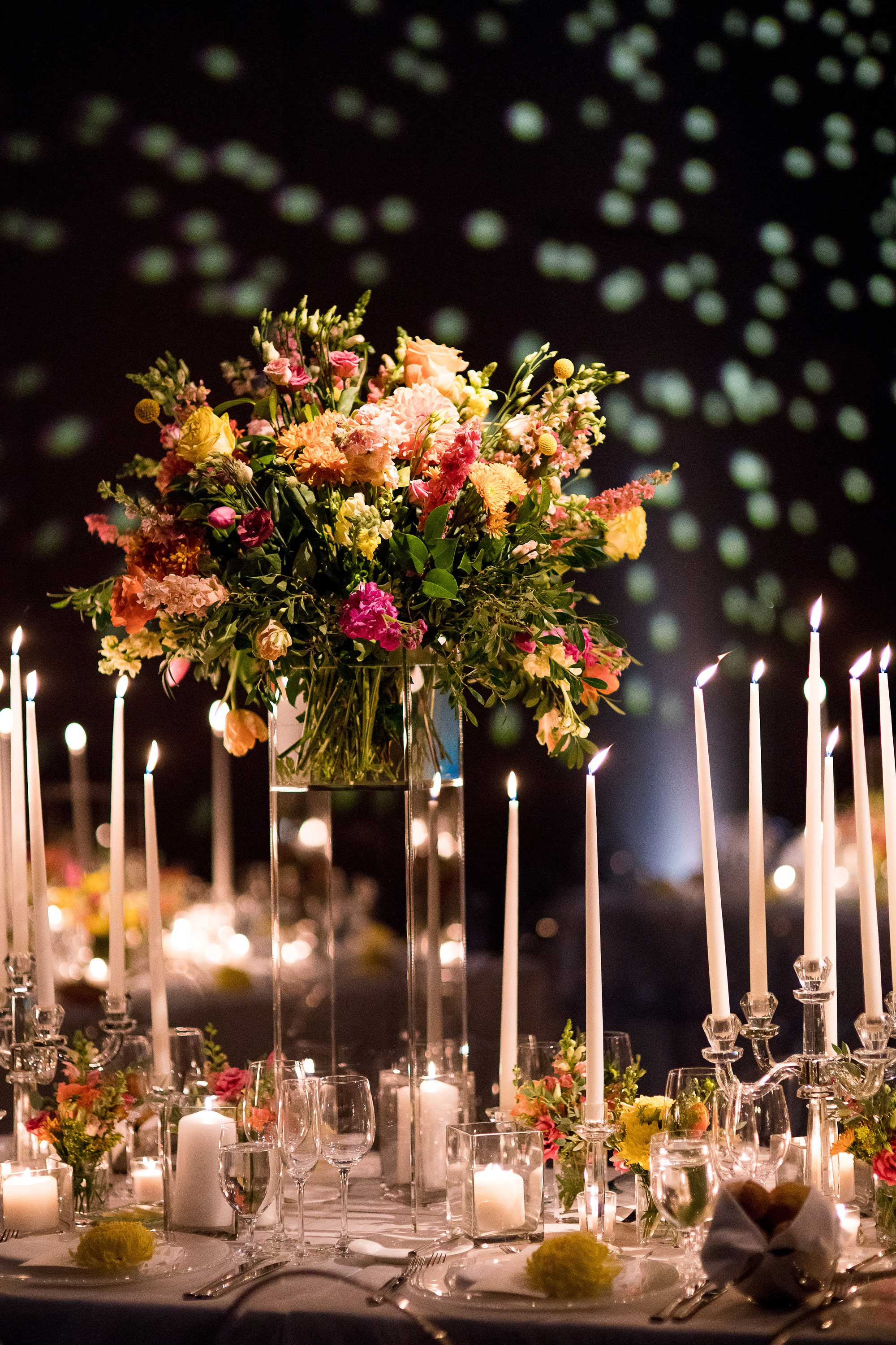 Inside Weddings Spring 2017 issue bright colored flower centerpiece with taper candles dark lighting reception