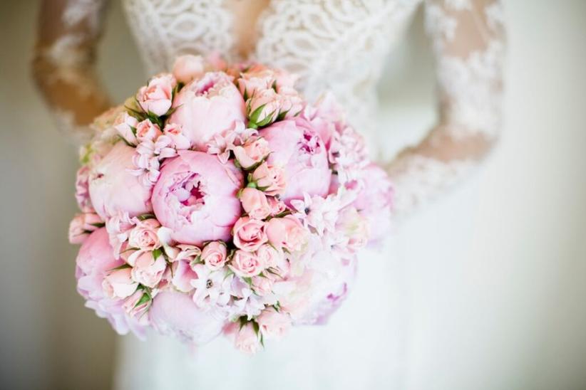 Bride in Carolina Herrera dress carrying pink peony bouquet