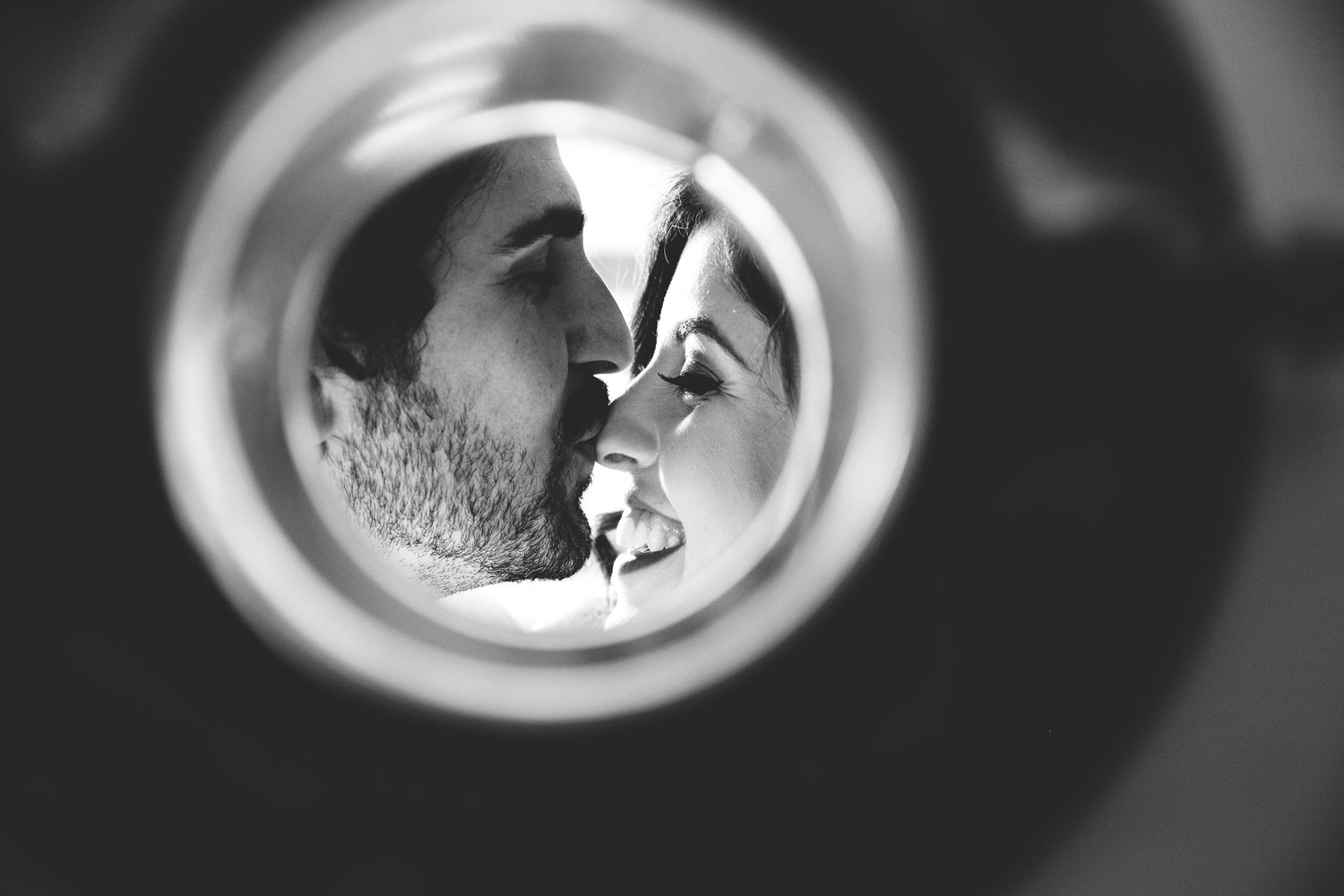 Artsy black and white engagement photo of groom kissing bride's nose