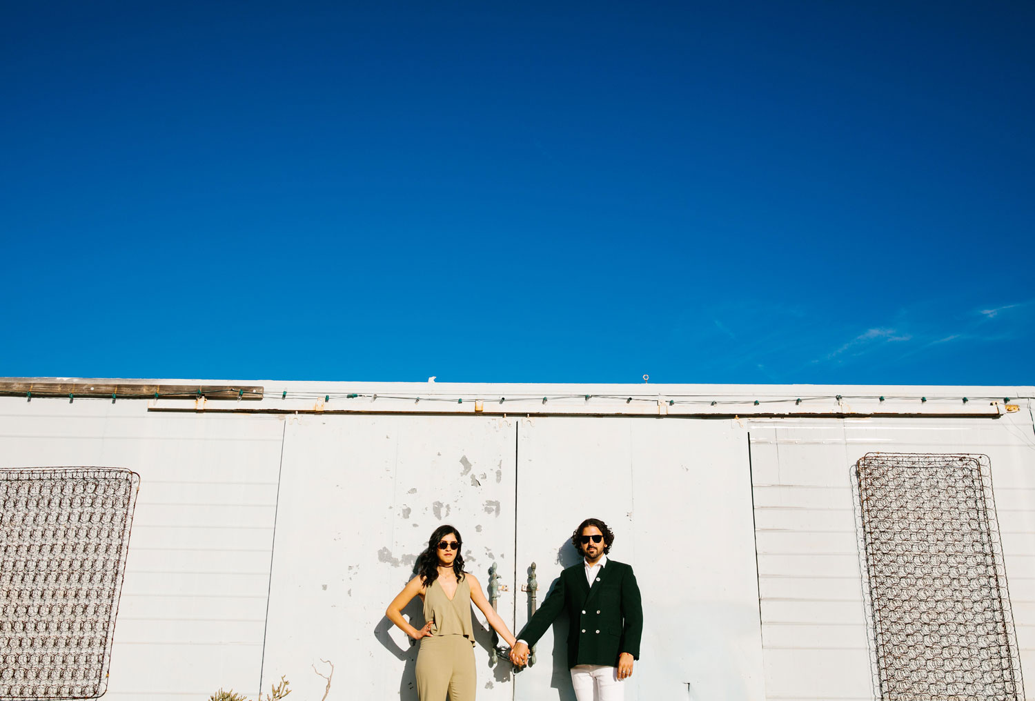 Bride and groom wearing sunglasses jumpsuit and blazer outfits Joshua Tree engagement shoot ideas