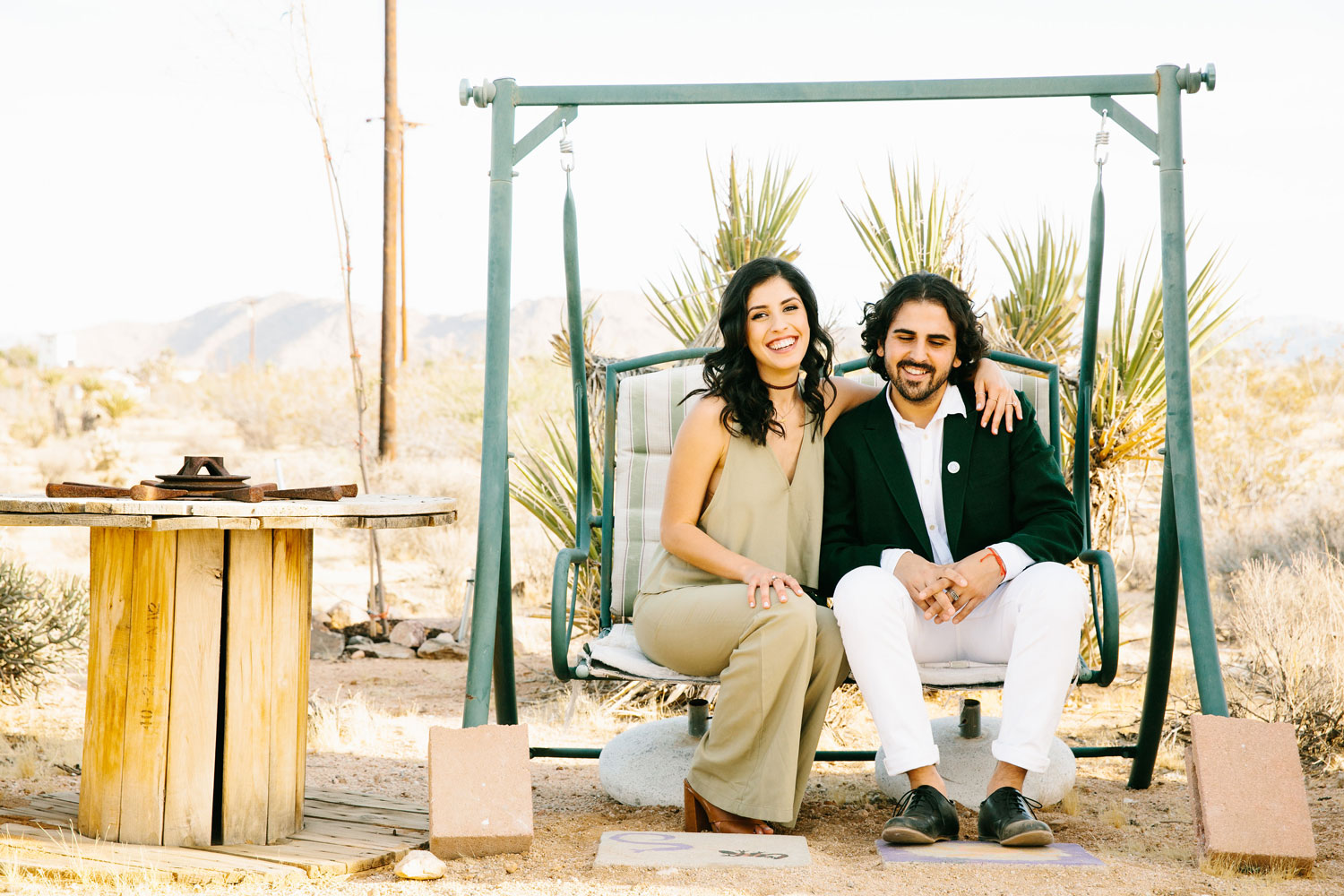 Bride in green jumpsuit with groom on antique swing bench Joshua Tree engagement shoot