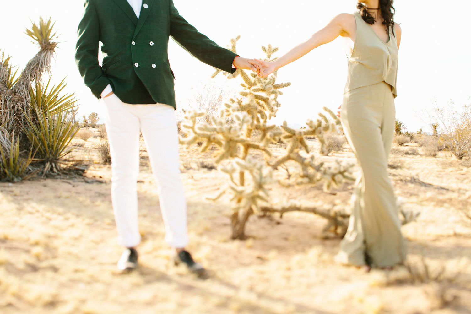 Groom in blazer and bride in jumpsuit Joshua Tree engagement shoot