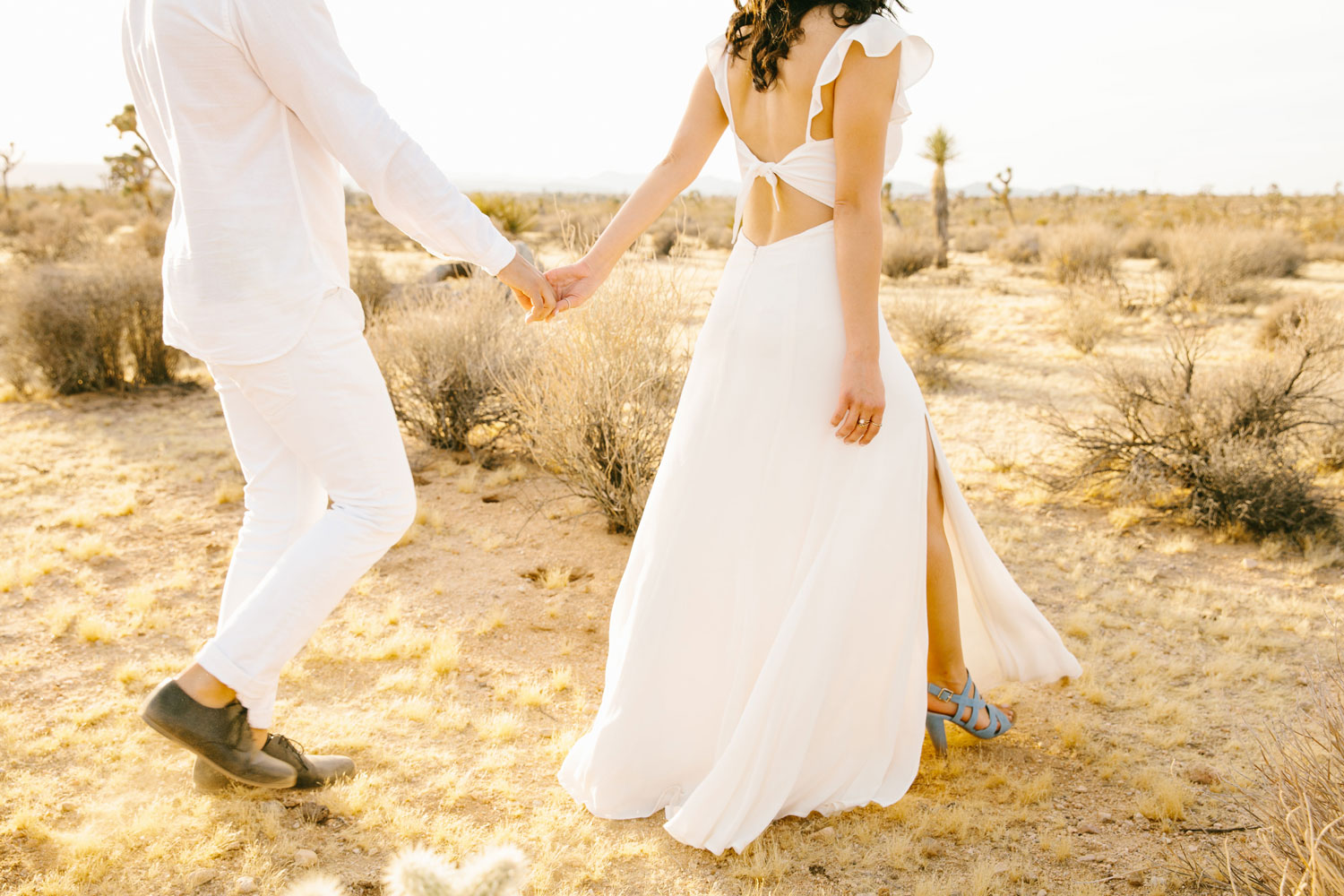 Close up of bride's open back dress and light blue shoes for engagement shoot Joshua Tree desert ideas