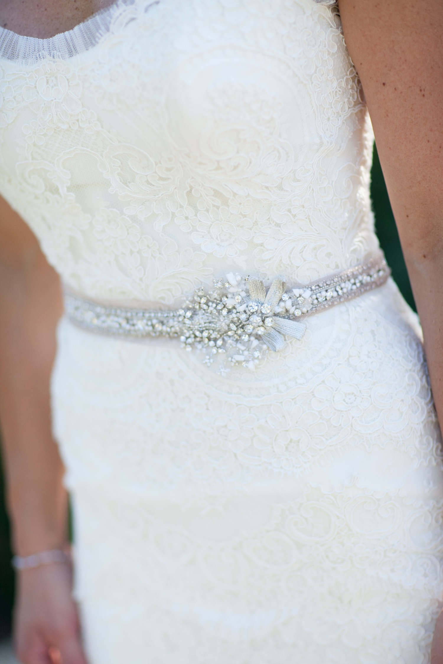 close up of strapless lace rivini wedding dress with beaded belt