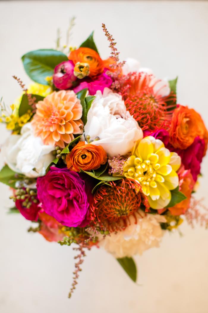 vibrant bridal bouquet with orange dahlias, ranunculus, fuchsia garden roses