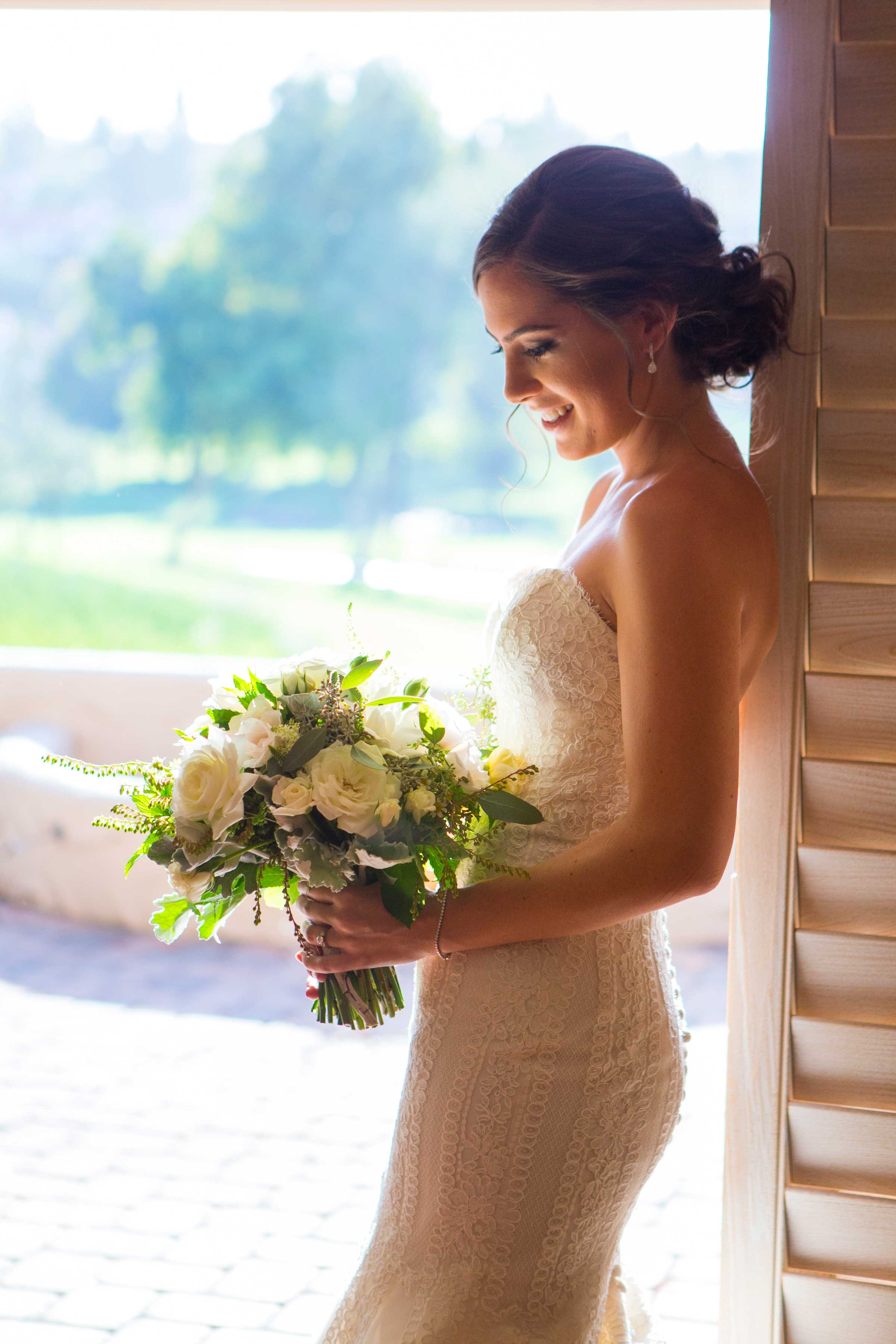 Bride holding bouquet before rustic wedding