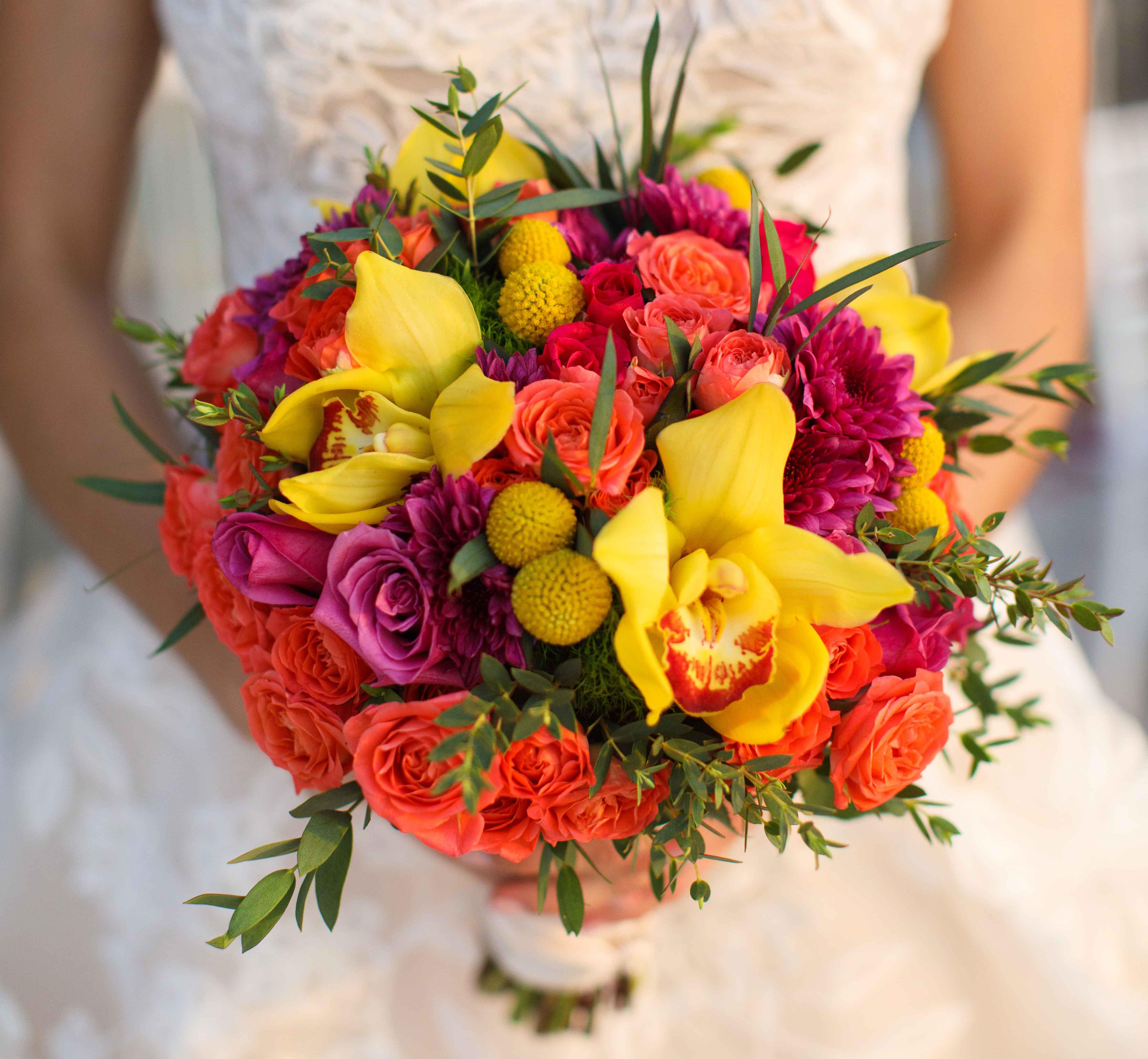 vibrant bridal bouquet with yellow orchids, orange and fuchsia roses