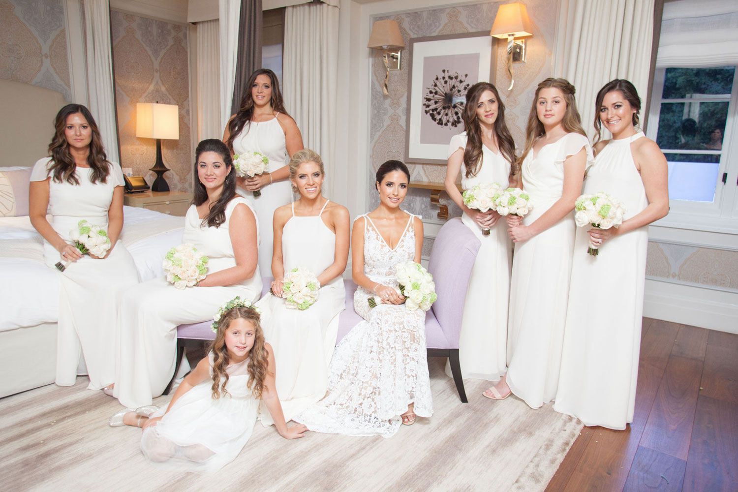 Bride in white dress and bridesmaids in white bridesmaid dresses in bridal suite