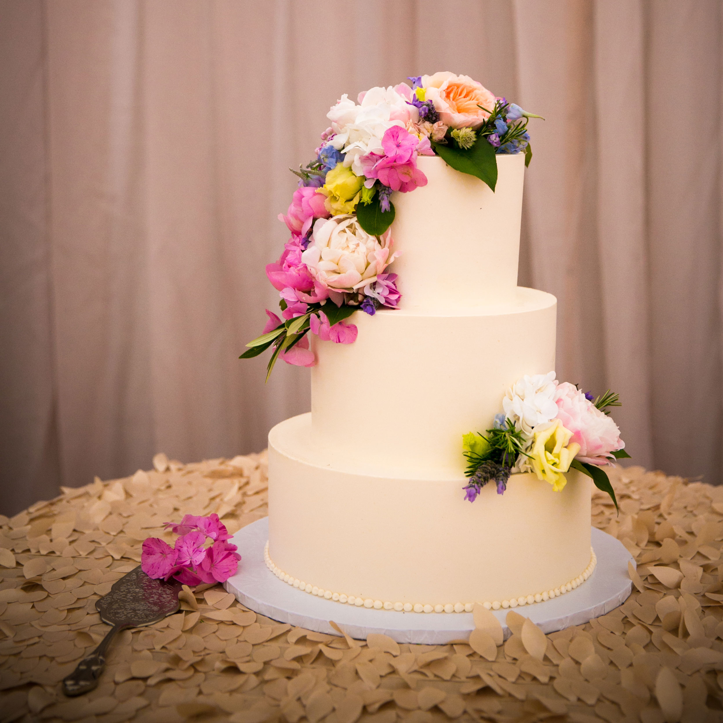 three-tier wedding cake with smooth frosting bright pink, blue, yellow fresh flowers