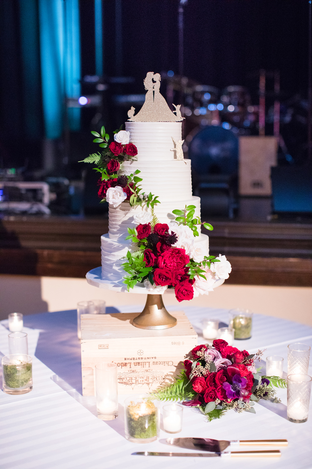 same-sex wedding cake, fresh flowers, red roses and ferns on four-tier wedding cake