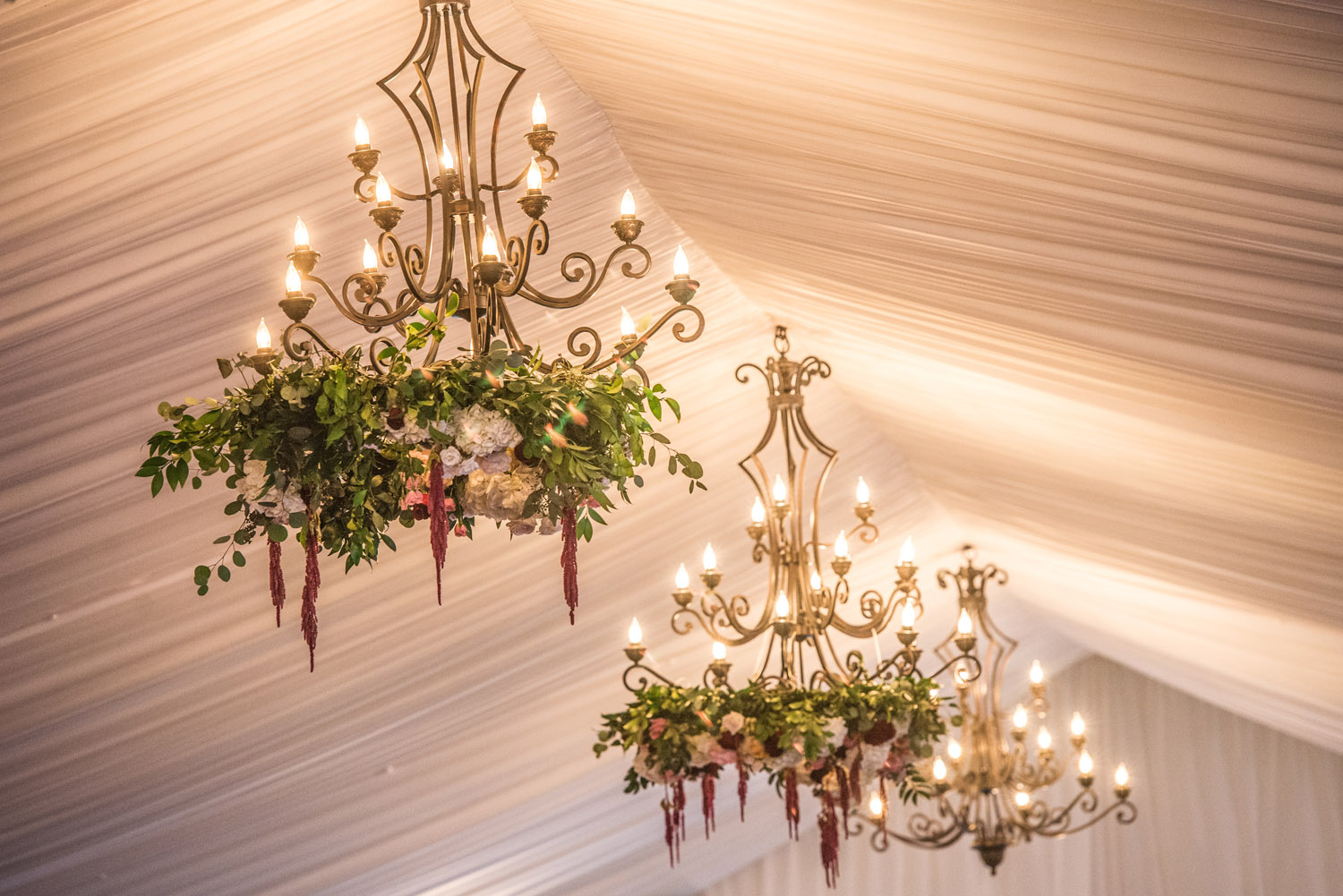 wedding reception chandeliers with floral and greenery accents