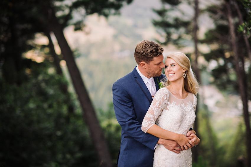 Bride in Oleg Cassini gown groom in navy blue suit forest wedding