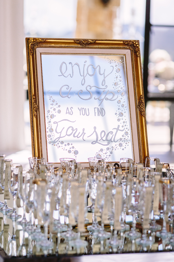 mirror sign saying champagne flutes are escort cards at wedding reception