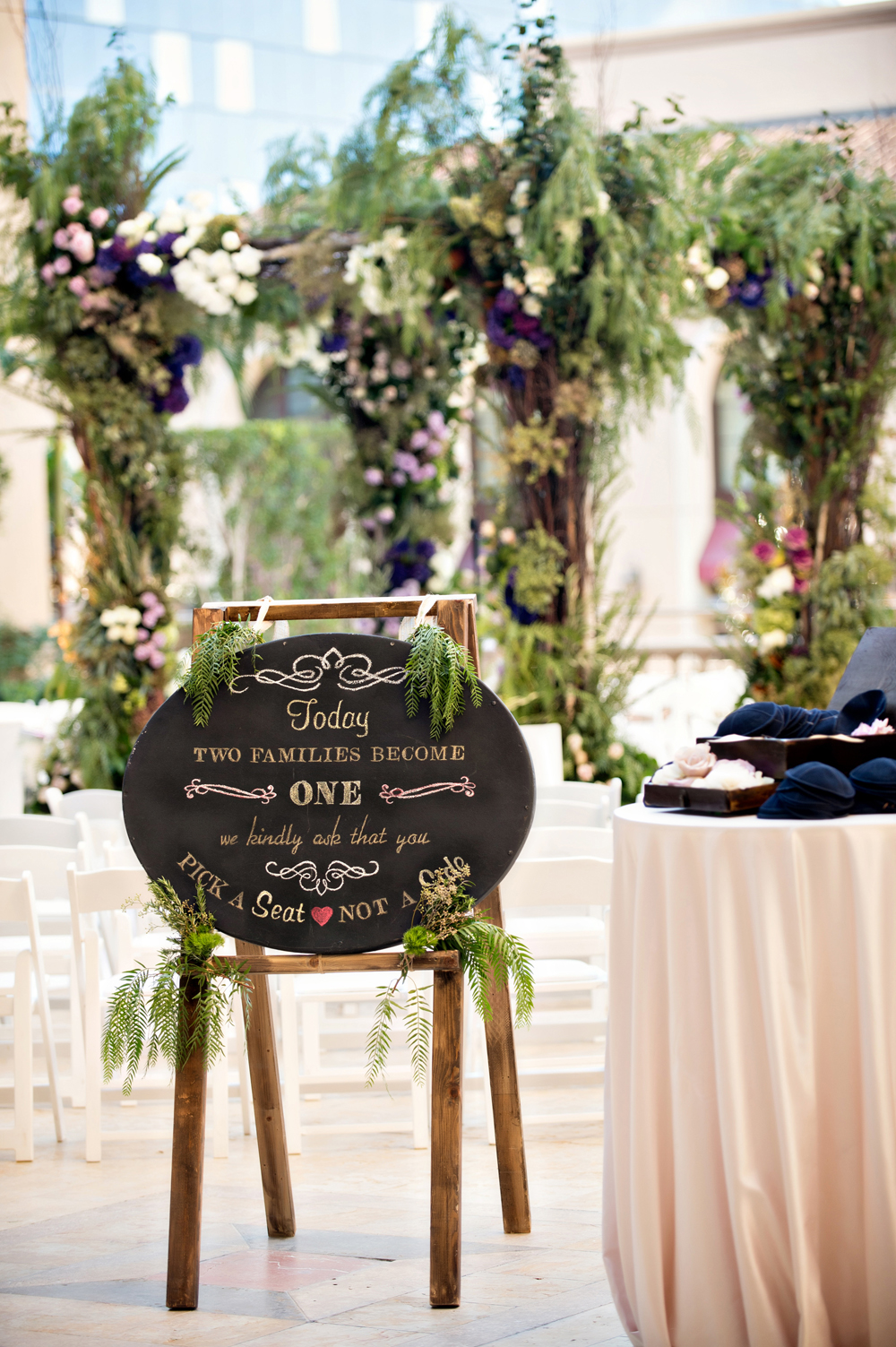 oval chalkboard sign on easle with greenery for wedding ceremony