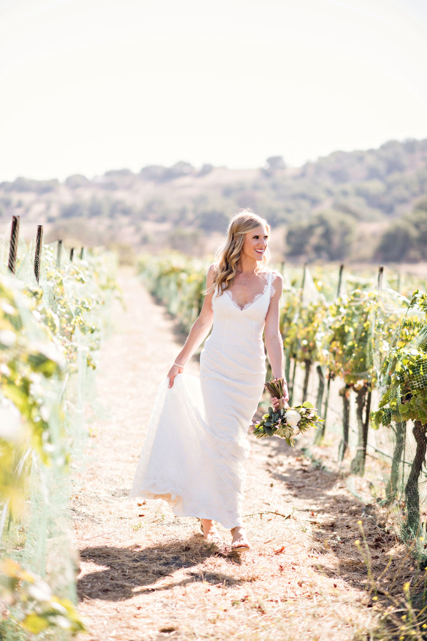 Laurie Bailey Photography bride in vineyard holding wedding dress sunny day