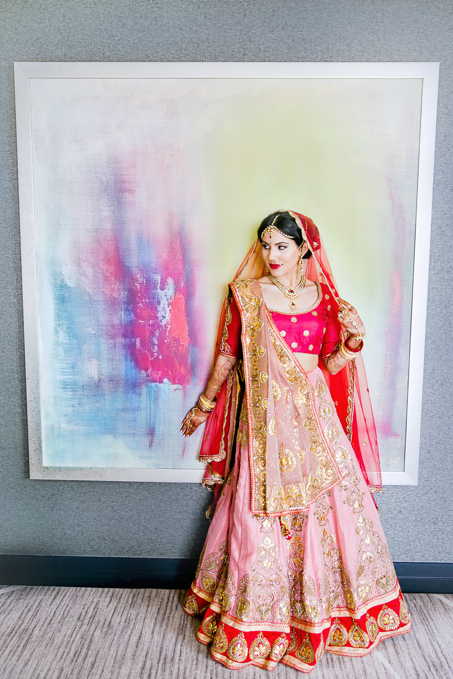 indian-american bride in red, blush, and gold sari