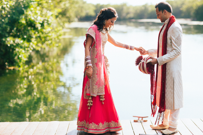 indian bride in red, blush, gold sari with groom in traditional attire, south asian first look