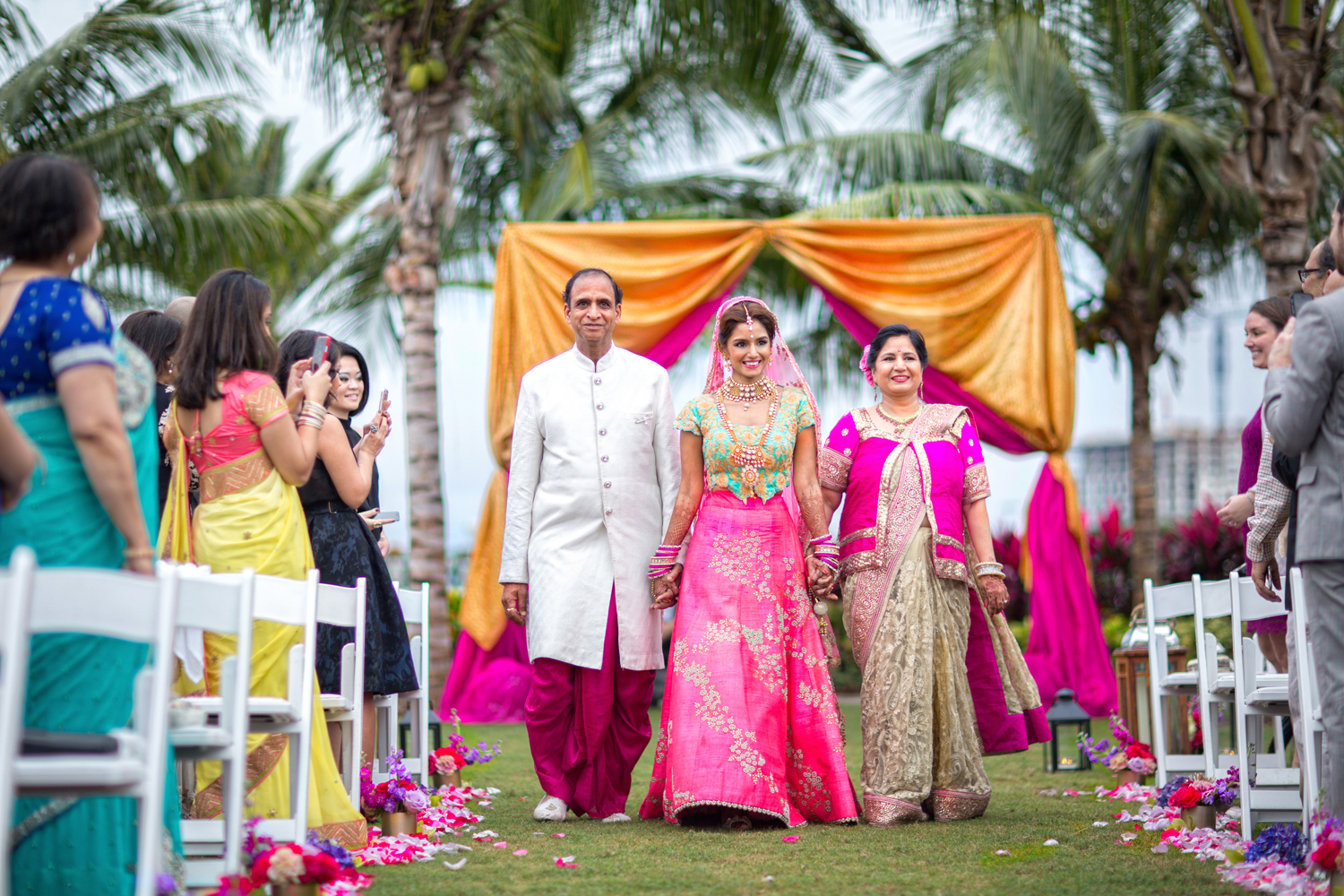 Indian bride in turquoise and pink sari and lehenga with parents walking down aisle