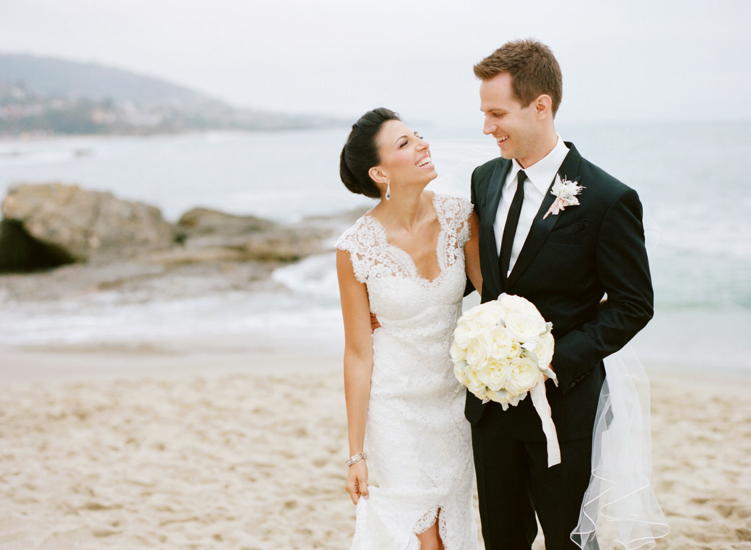 Bride and groom walking on beach in Laguna Beach