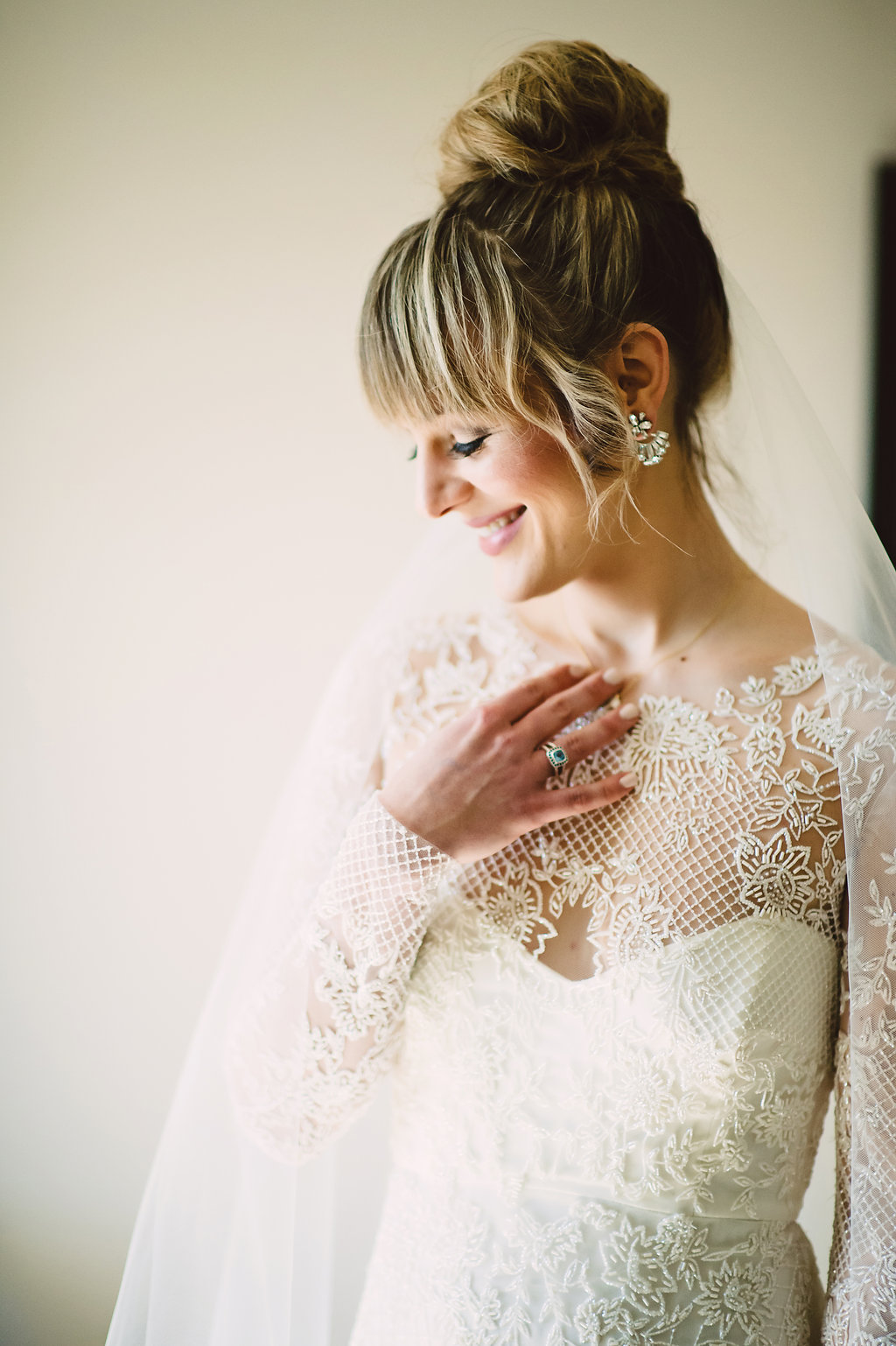 bridal updo, messy top knot, bridal top knot, blonde bride with bangs and top bun