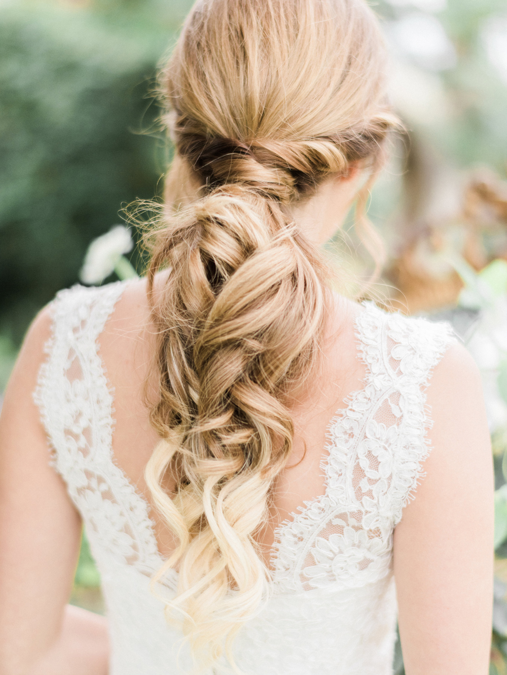Long hair tied back into low curly pony tail relaxed wedding hairstyle