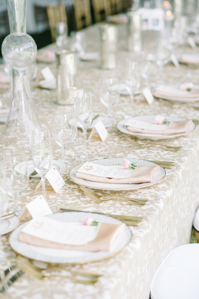 Light neutral patterned linens at wedding reception long table