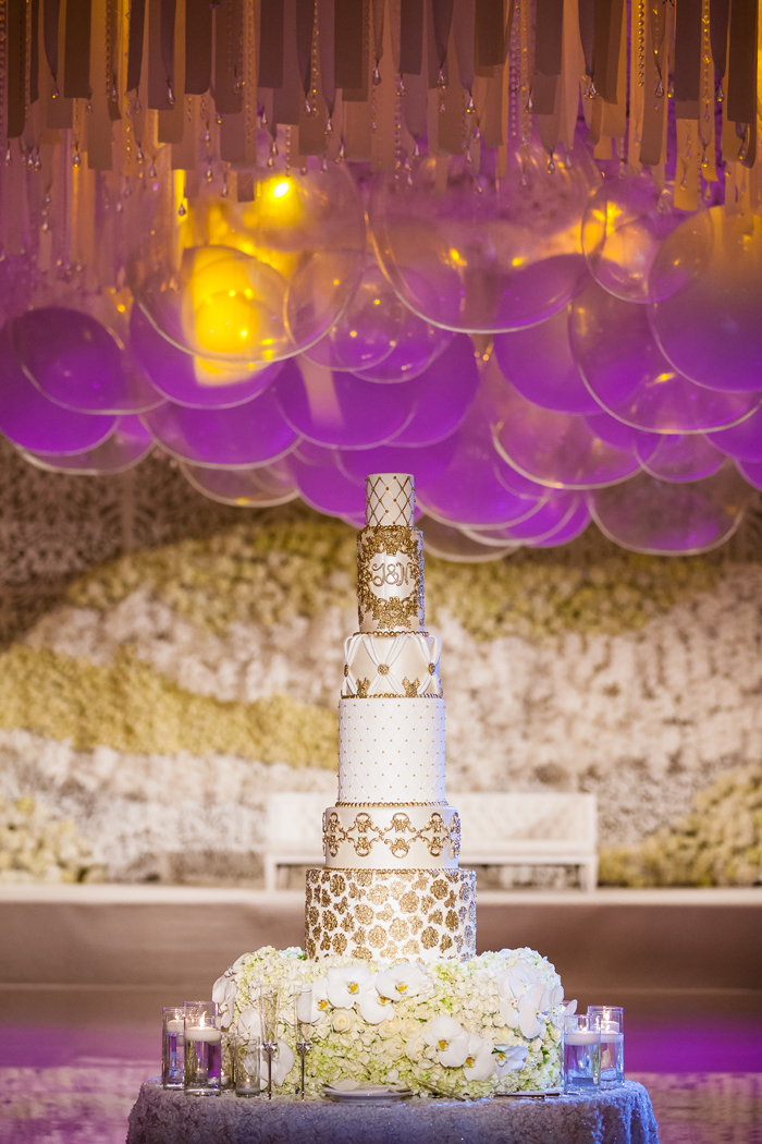 Tall white cake with gold detailing at wedding cake ideas