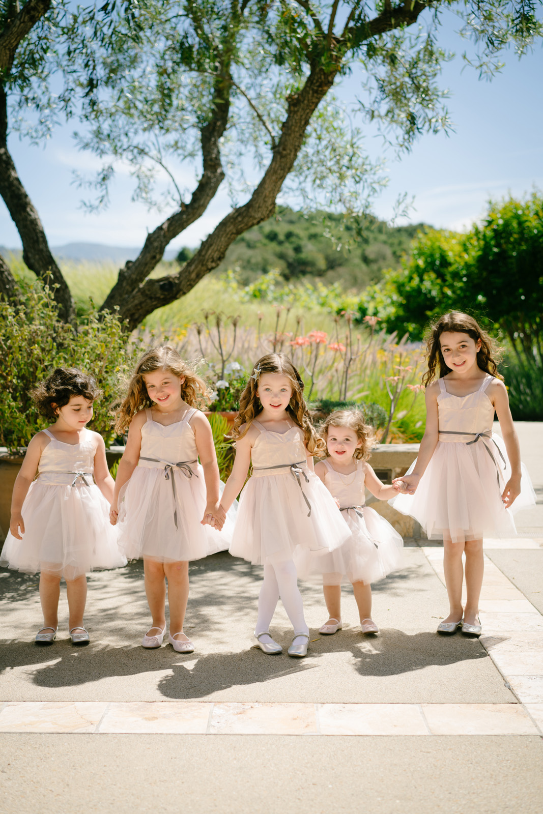 Flower girls holding hands with ribbon belts at outdoor wedding