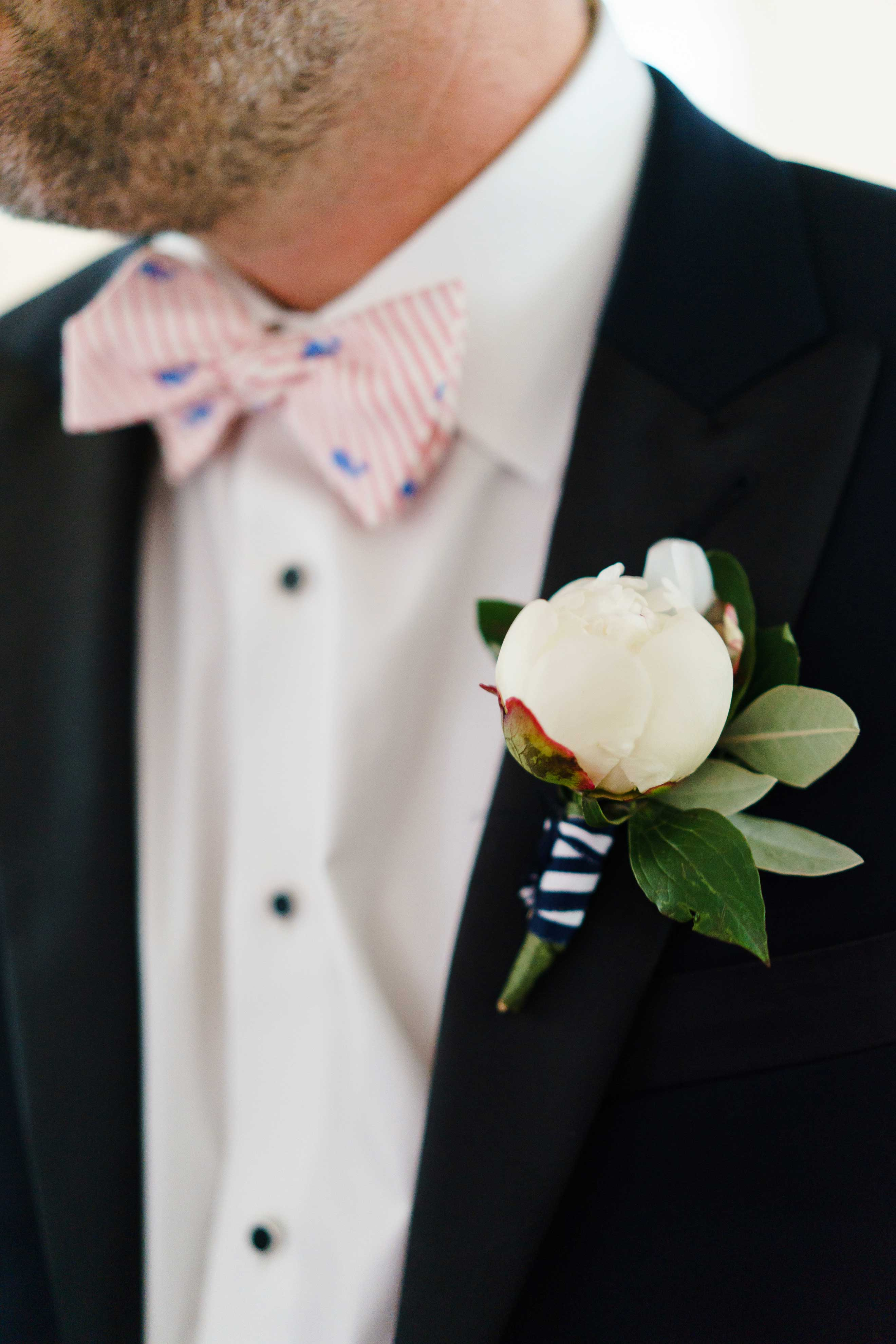 Groom wearing pattern bow tie and peony bud boutonniere