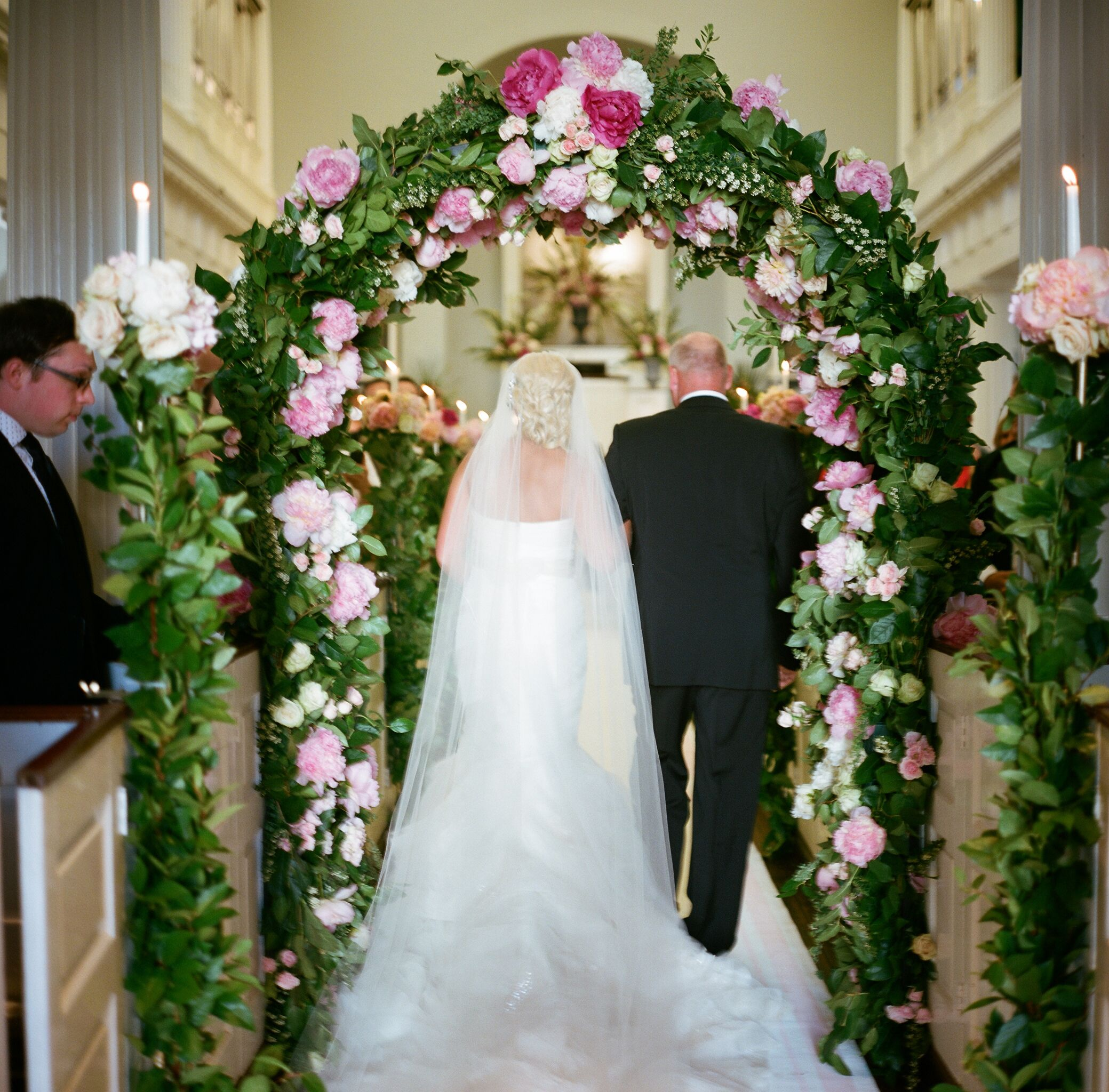 Bride walking with father under ceremony arch of greenery and pink peonies