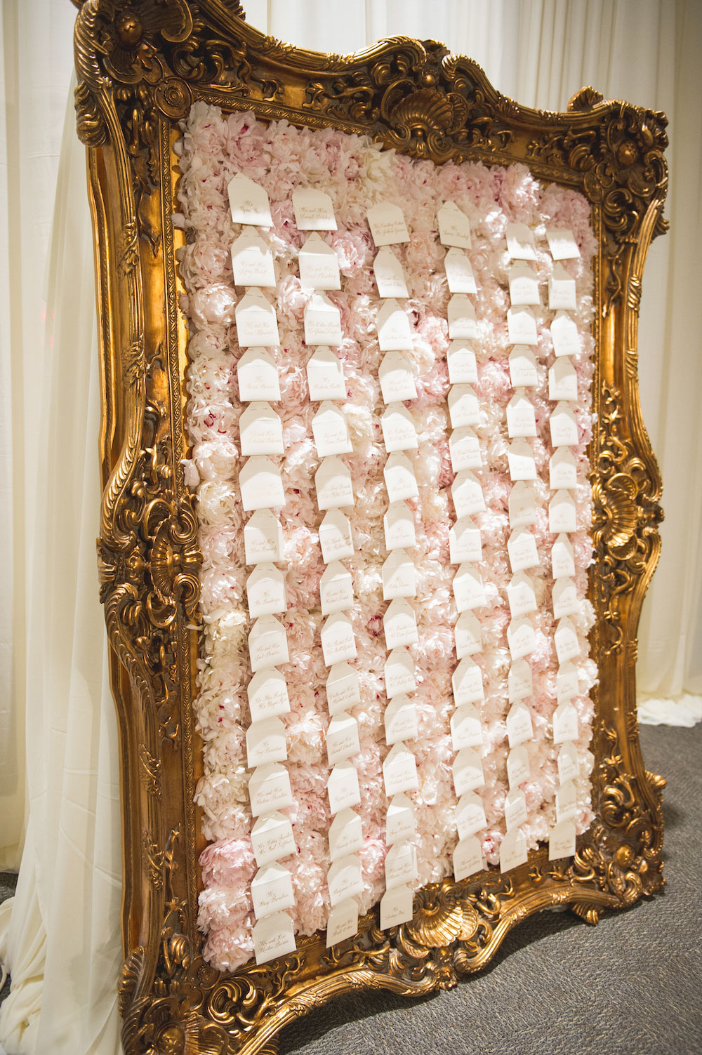Gold frame with wall of pink peony flowers escort cards attached