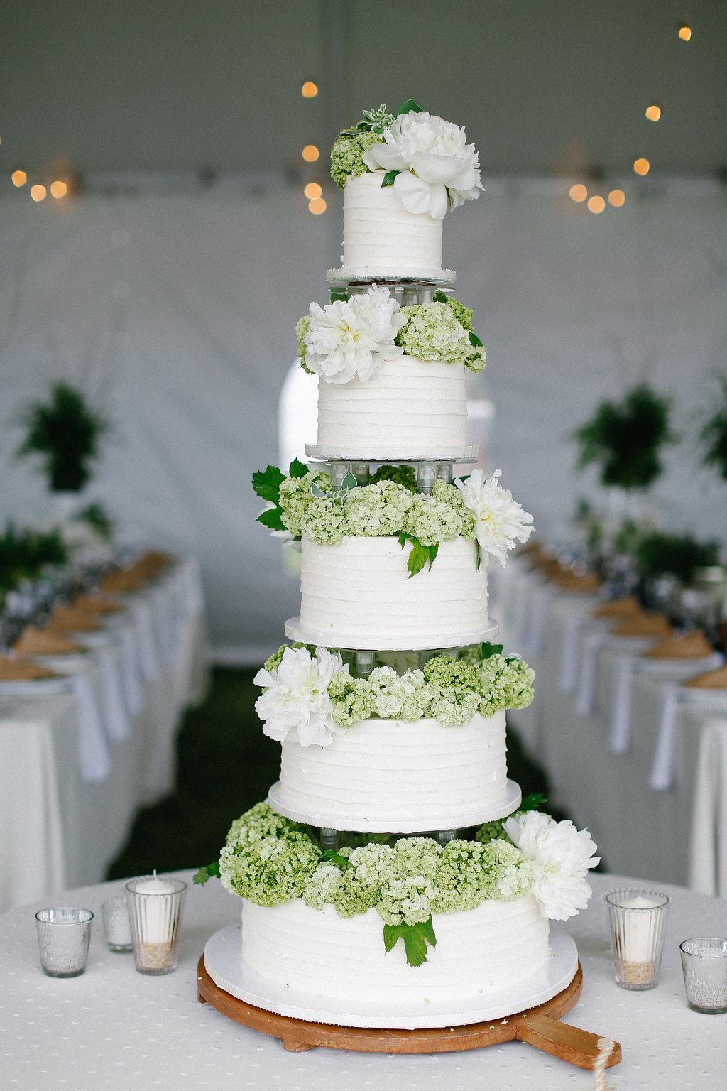White tall wedding cake with fresh green hydrangea and white peony flowers