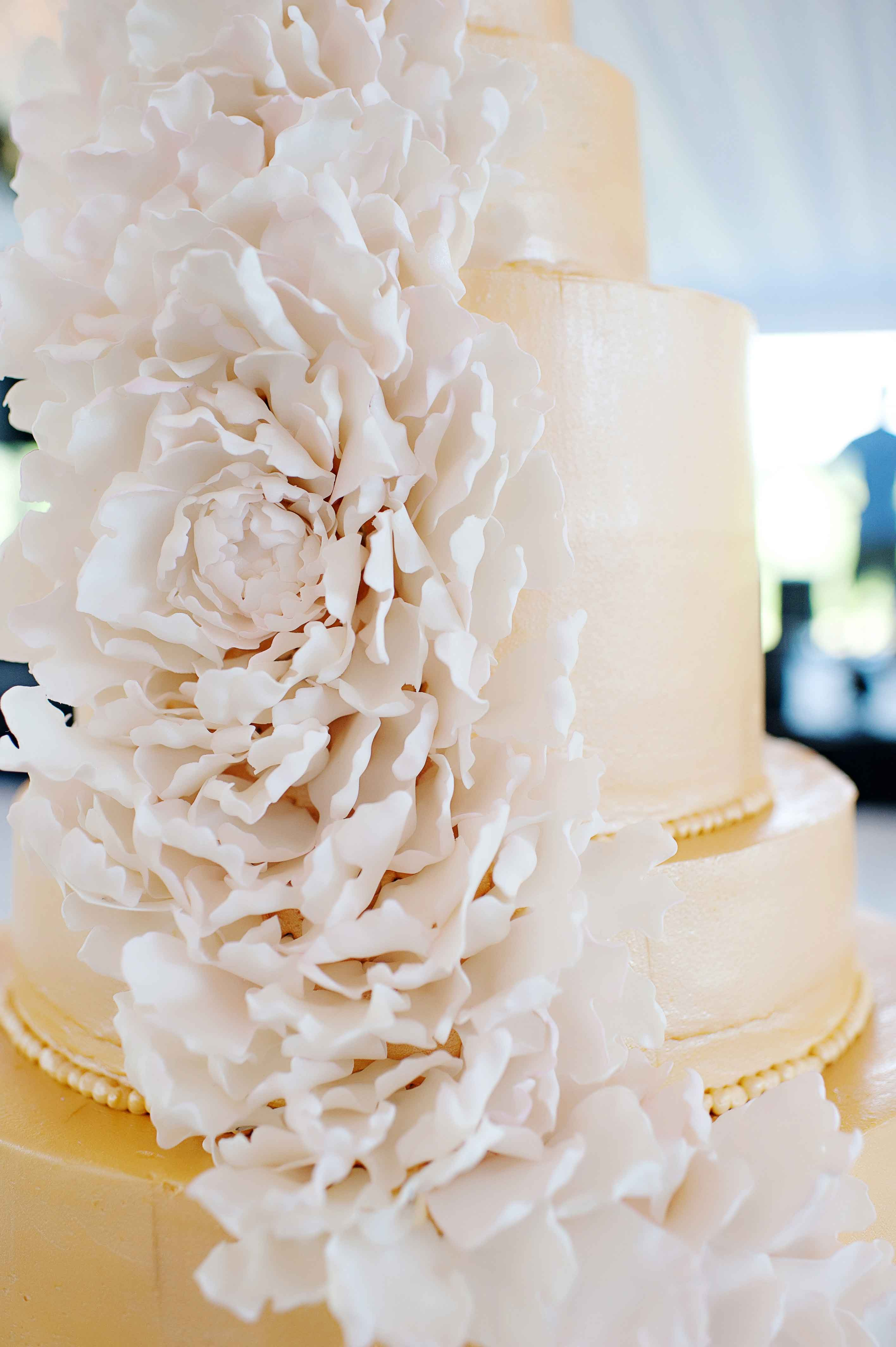 White wedding cake with cascading sugar flower down side