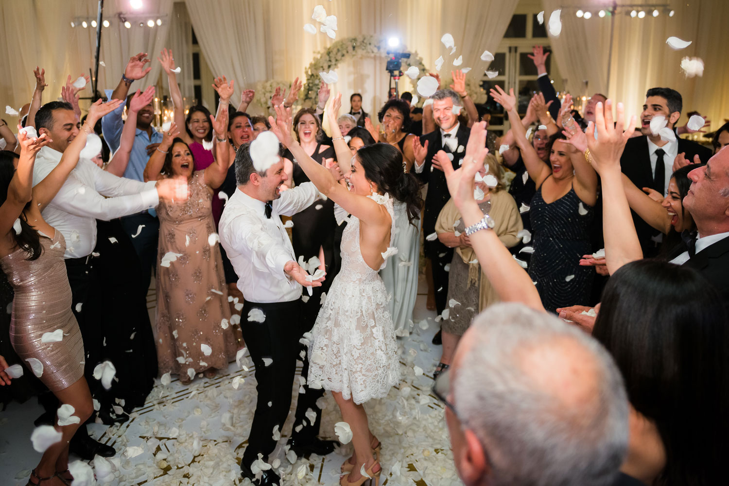 candid shot of wedding guests dancing and throwing rose petals at bride and groom