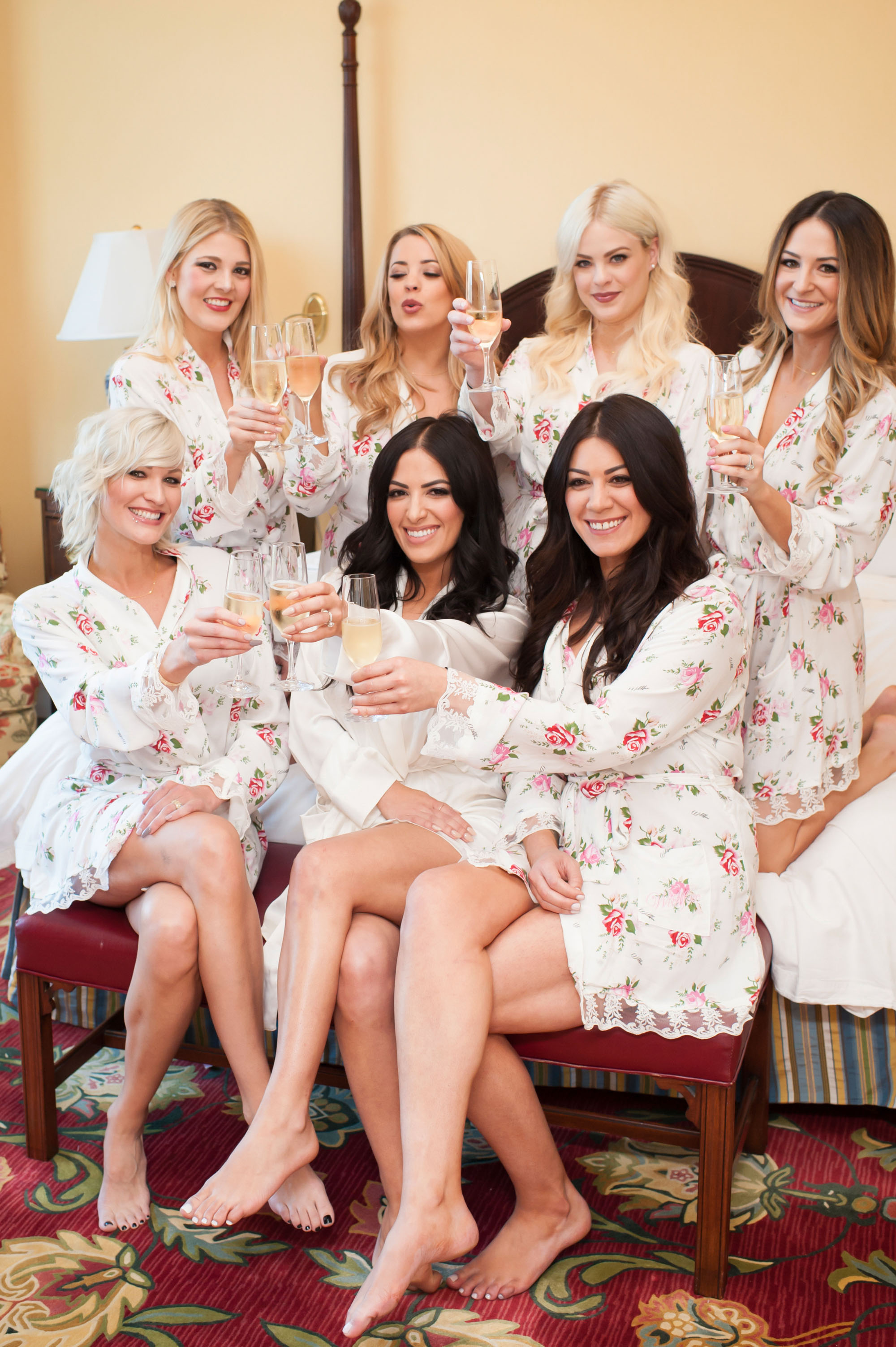 Bride and bridesmaids getting ready in bridal suite with champagne