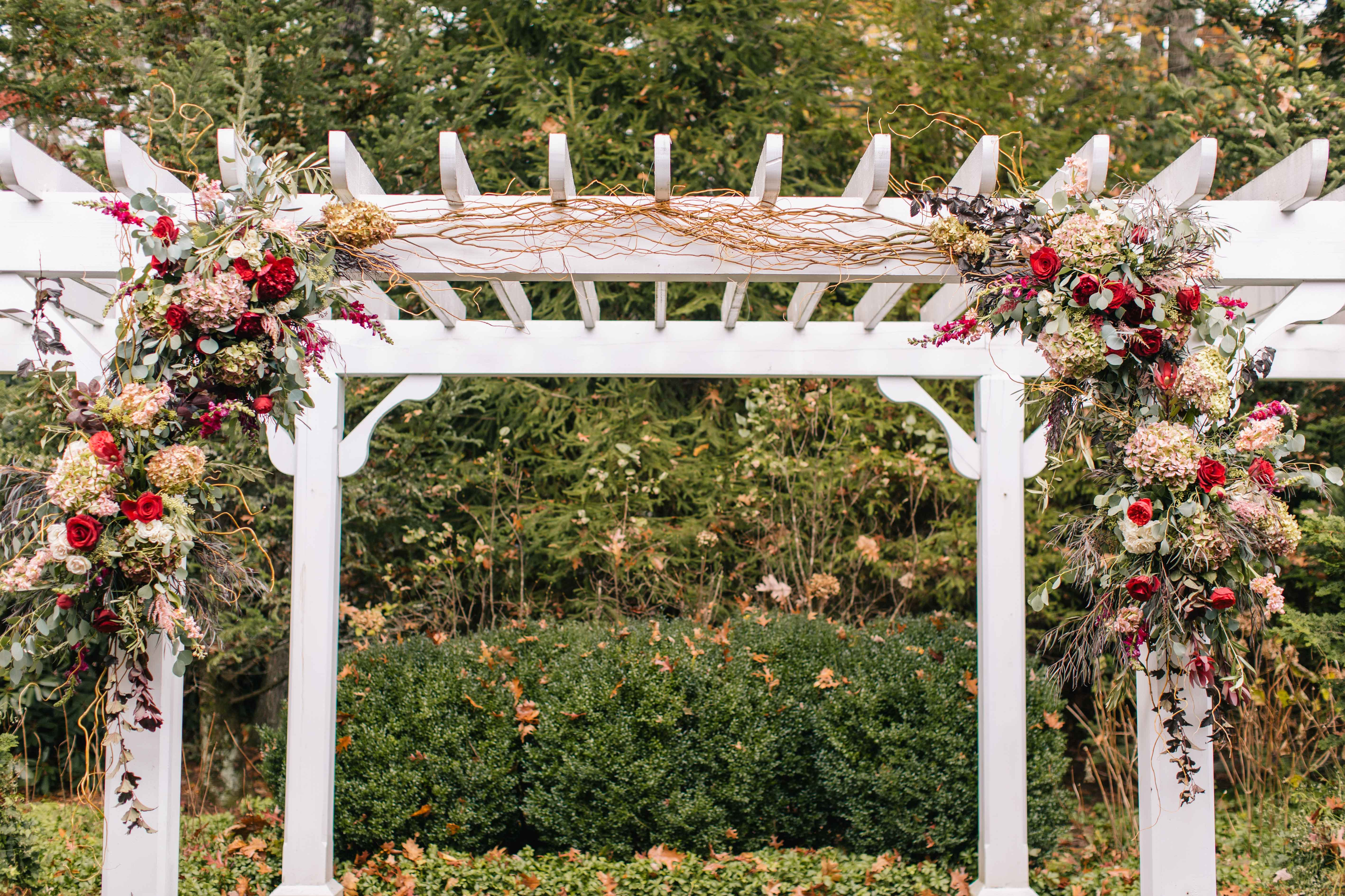 Ceremony arbor with fall hued colors wedding flowers