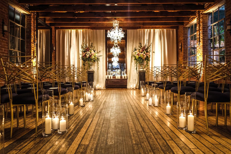 Wood plank wedding ceremony fall decor dark flowers candlelight