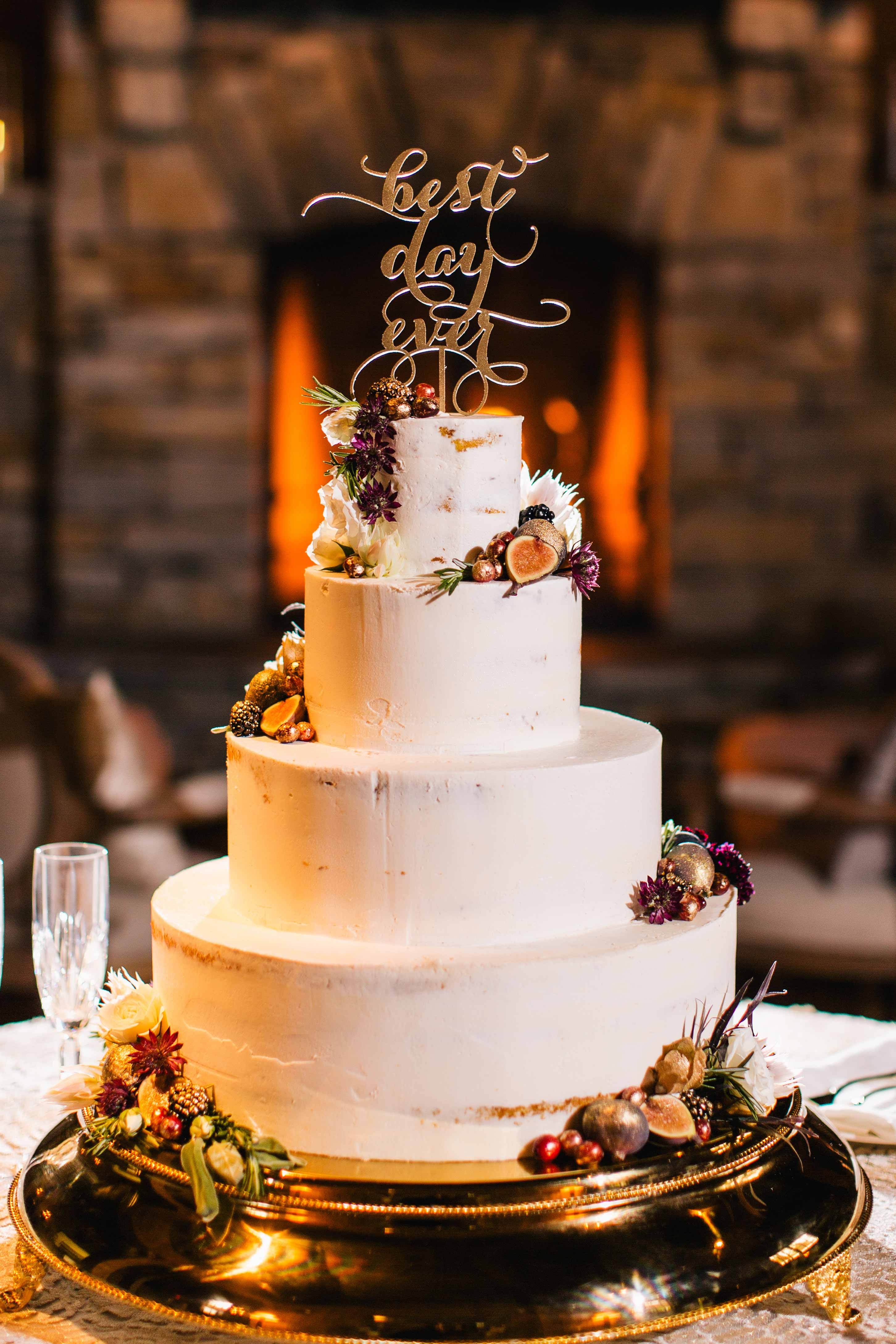 Fall theme semi naked cake with fresh fruit and fall colored flowers