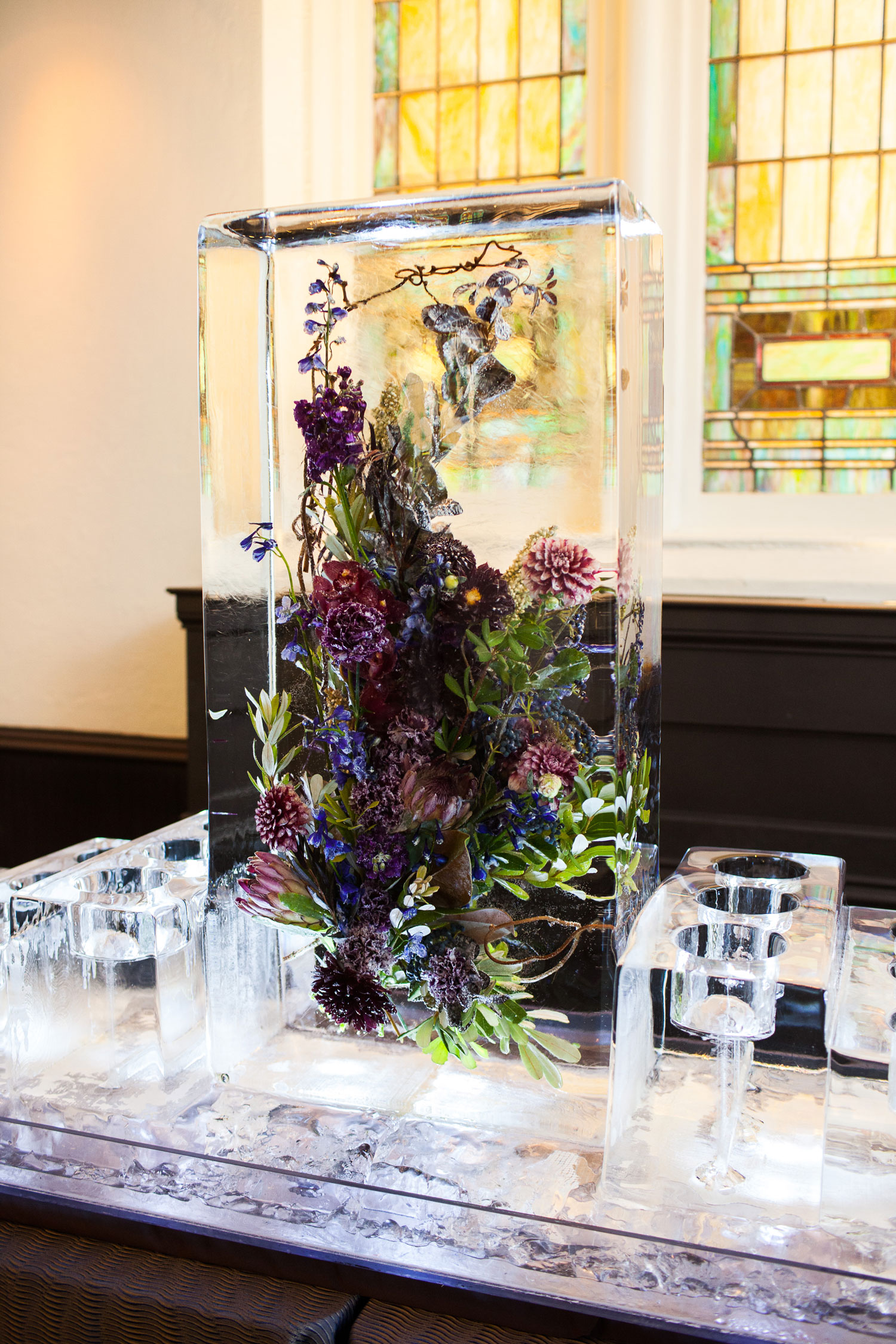 Flower arrangement in ice sculpture wedding reception stained glass