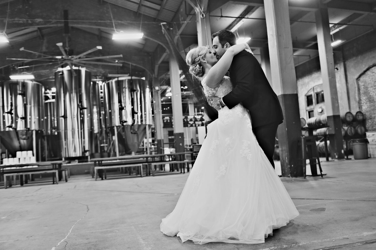 Bride and groom kiss in beer brewery wedding portrait