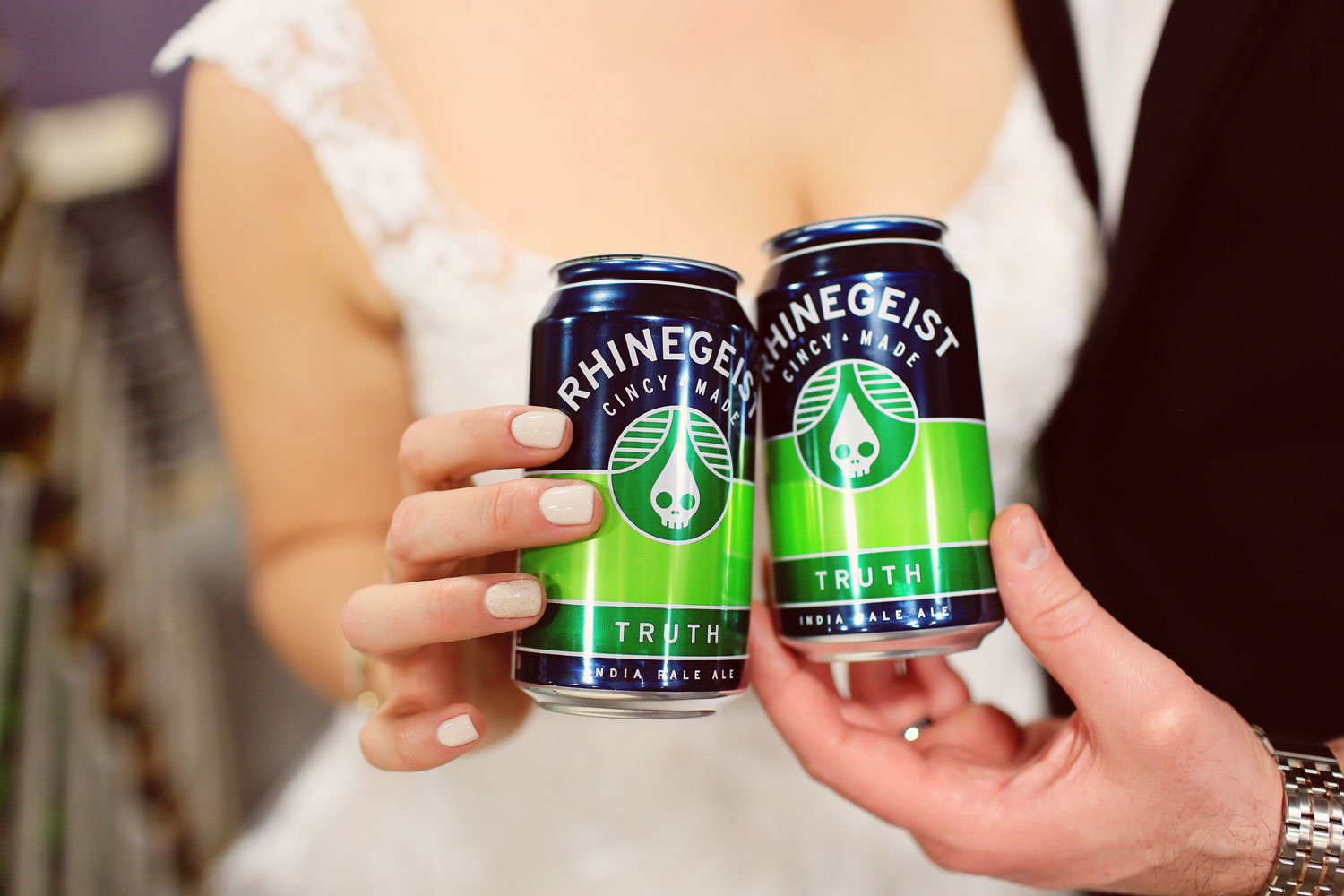 Bride and groom toast cans of beer at brewery wedding venue