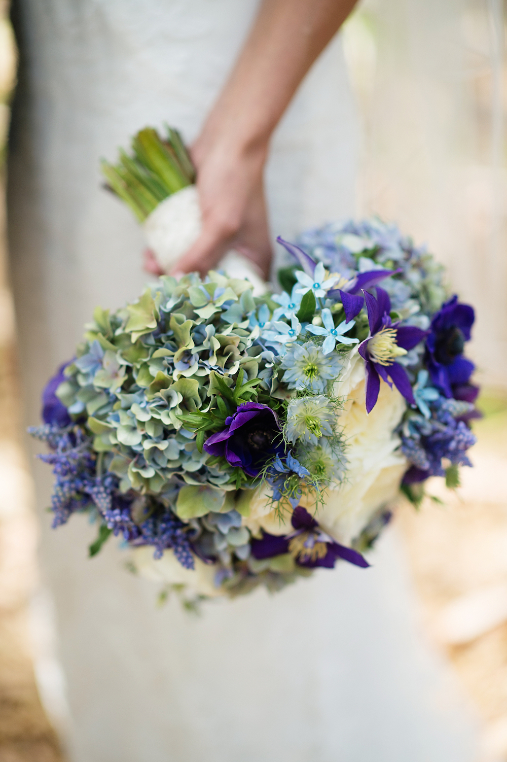 Bride in wedding dress with almost all blue wedding bouquet