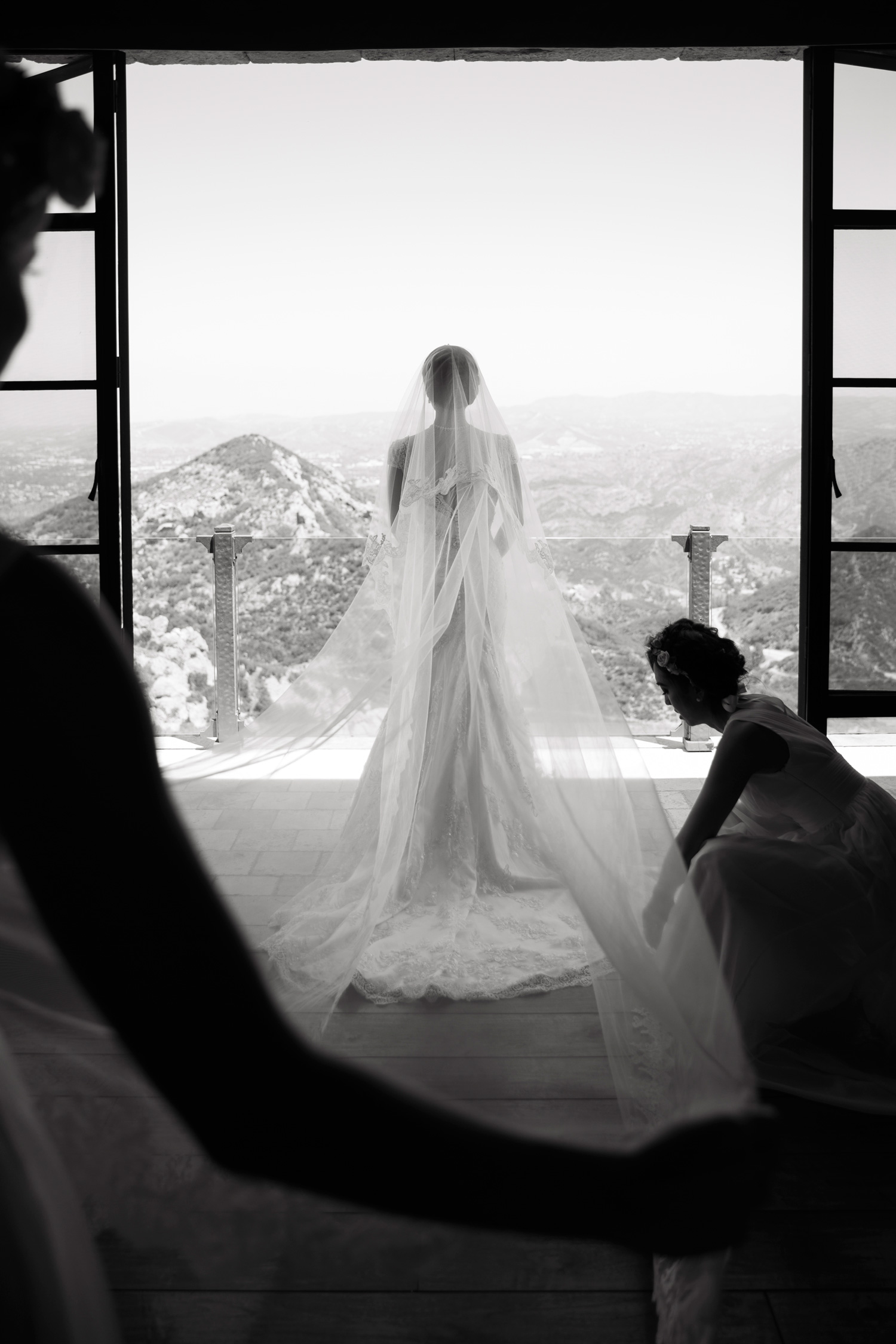 Black and white photo of bride looking out window balcony wedding photos
