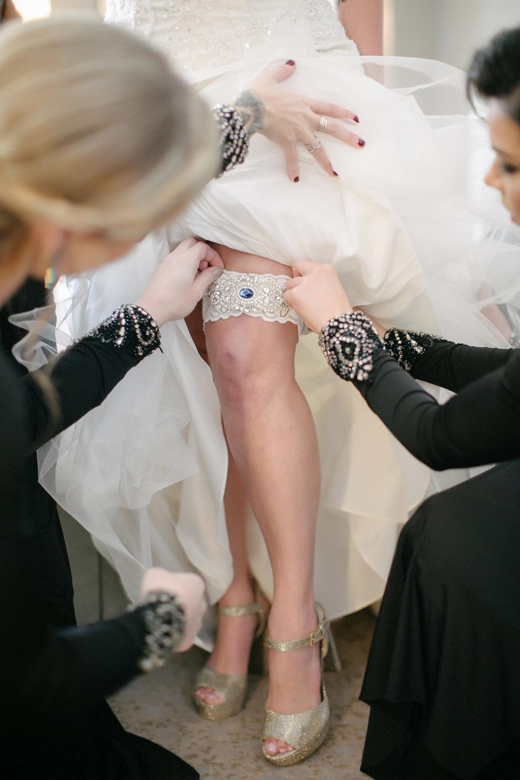 bridesmaids put garter on bride, garter with blue jewel