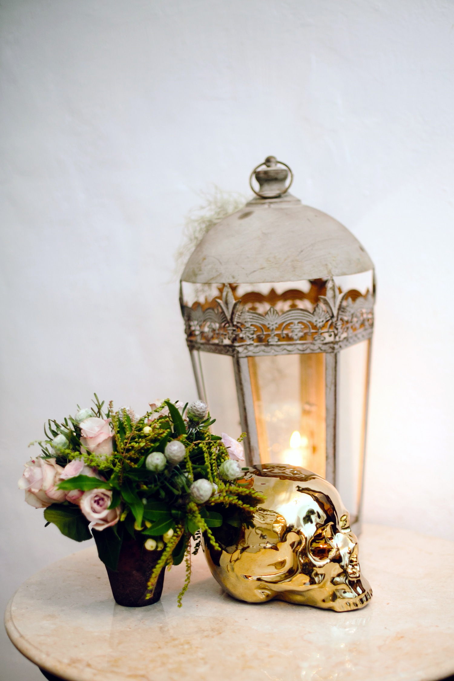 Gold skull wedding decor next to lantern halloween wedding ideas