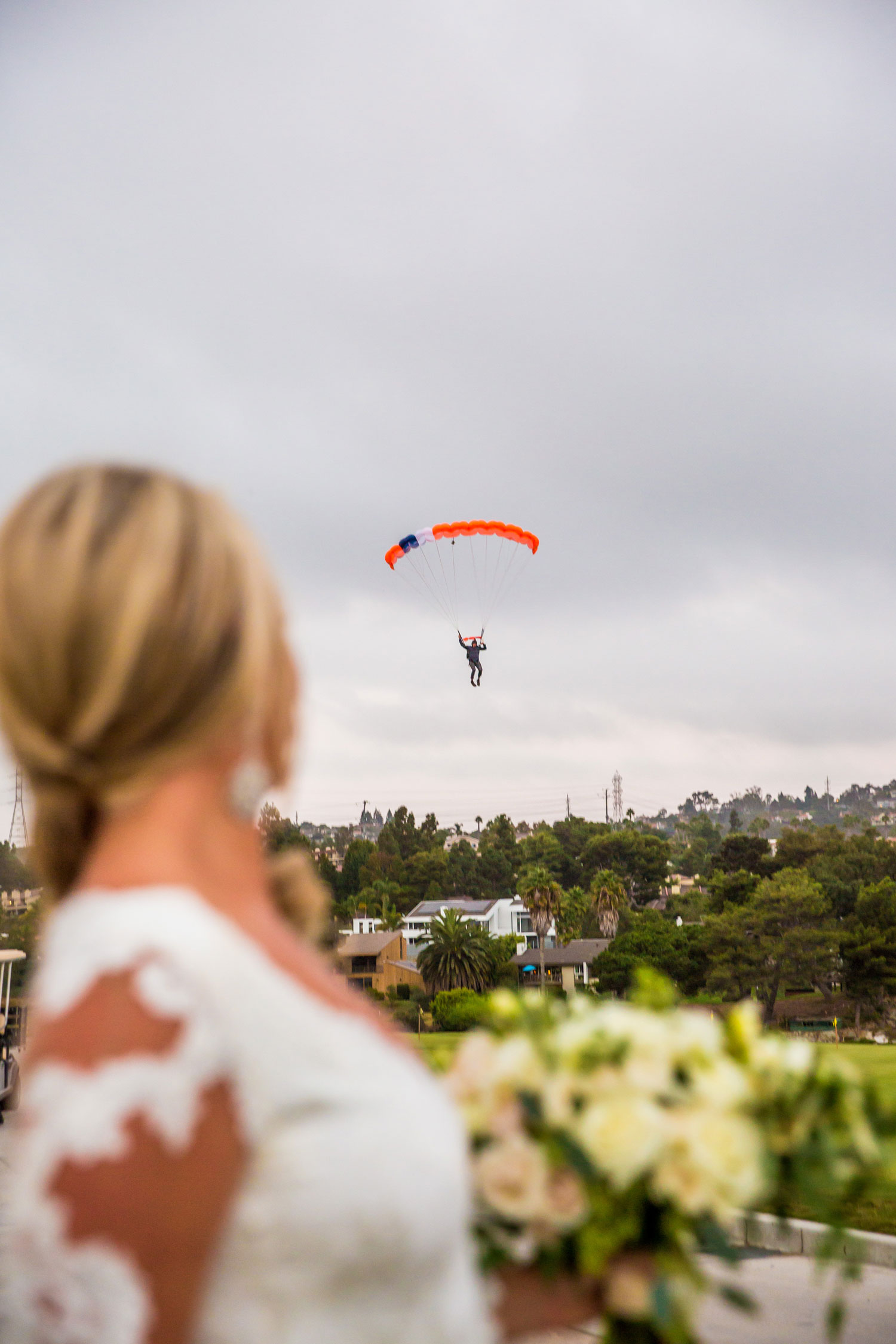 Bride watching groom skydive into wedding cocktail hour