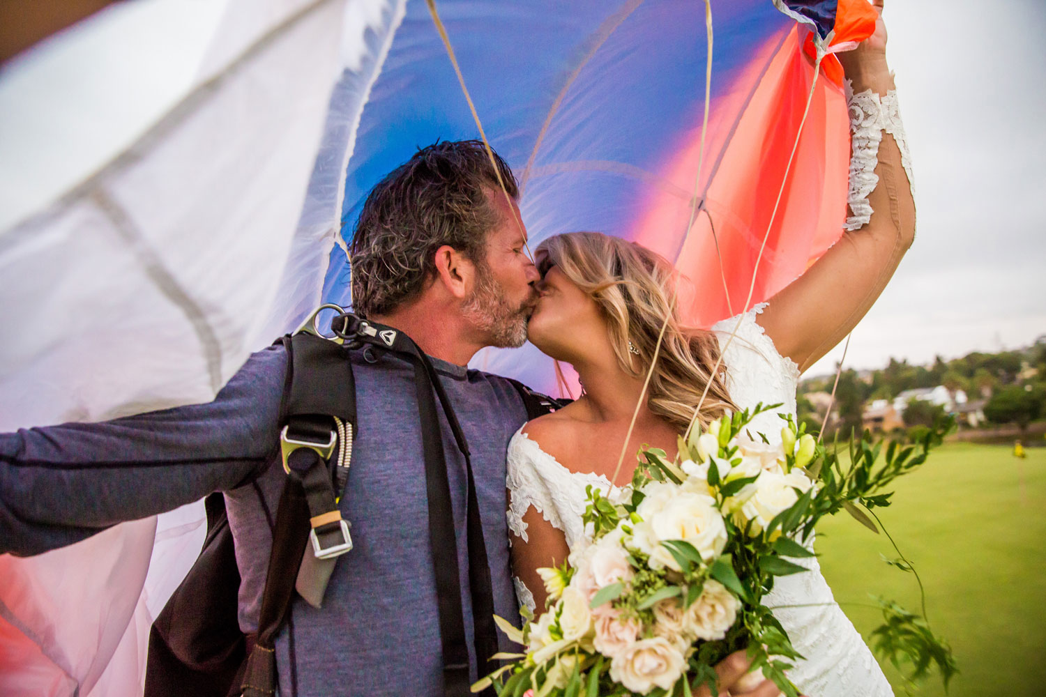 Bride and groom kiss under parachute wedding cocktail hour surprise