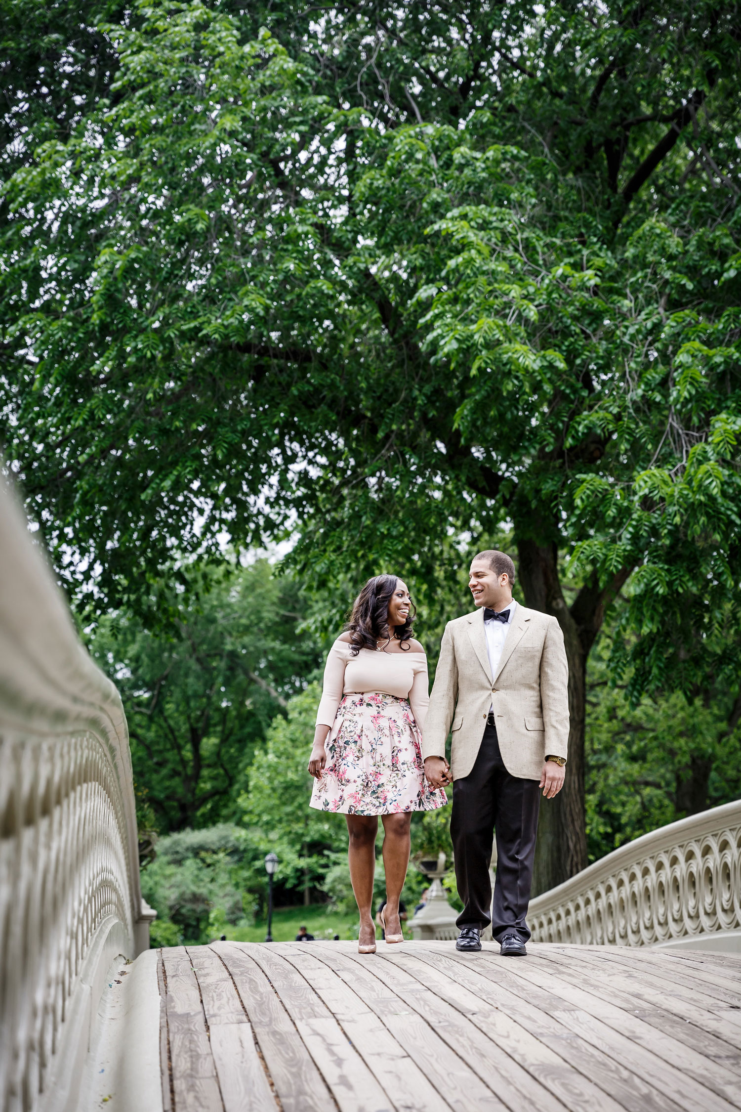 New York City central park engagement session photo by Amy Anaiz walking on bridge