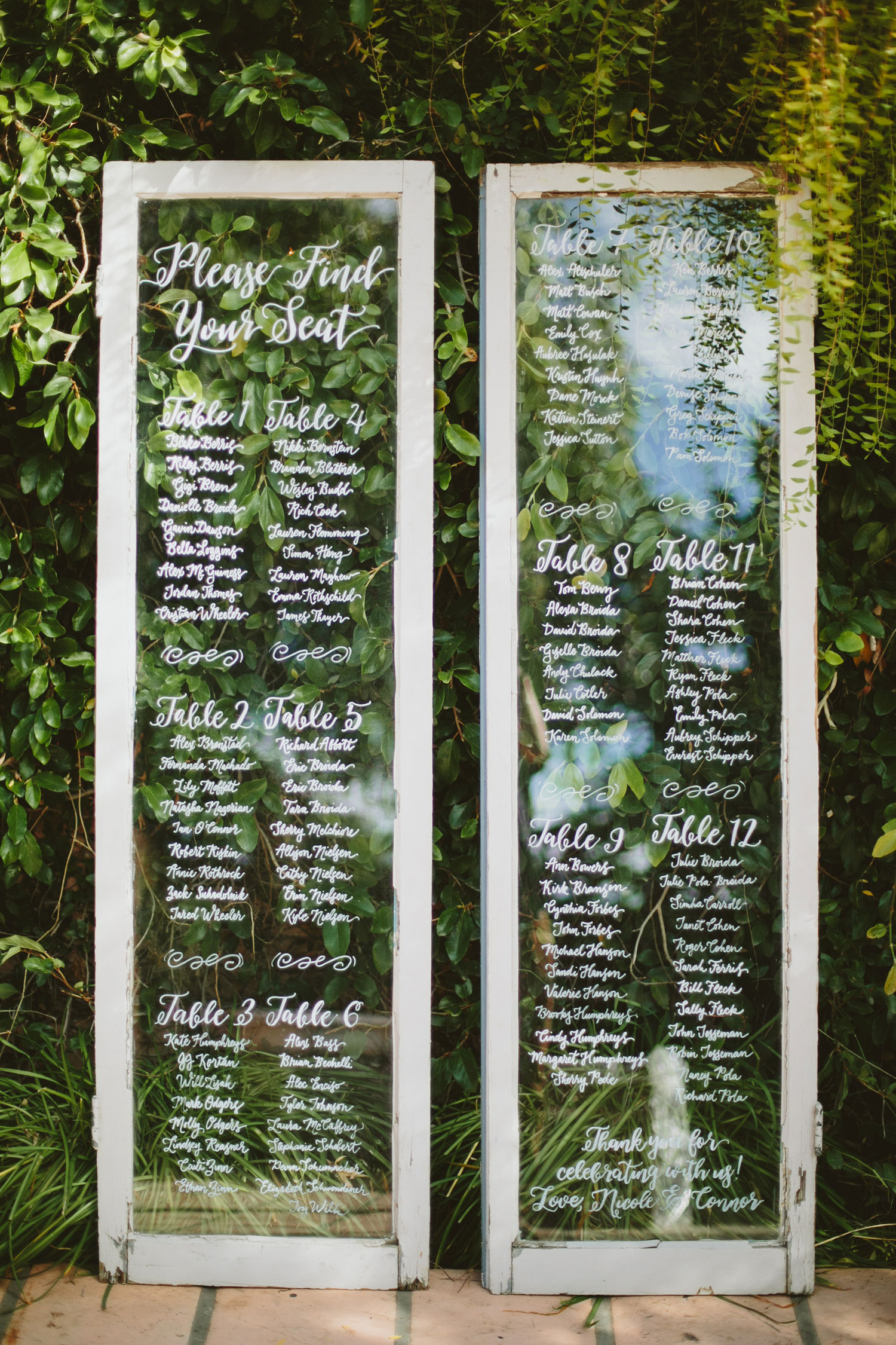 Tall rustic window seating chart with calligraphy on glass