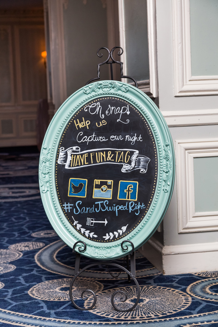 How they met wedding hashtag in chalkboard sign frame blue outside reception